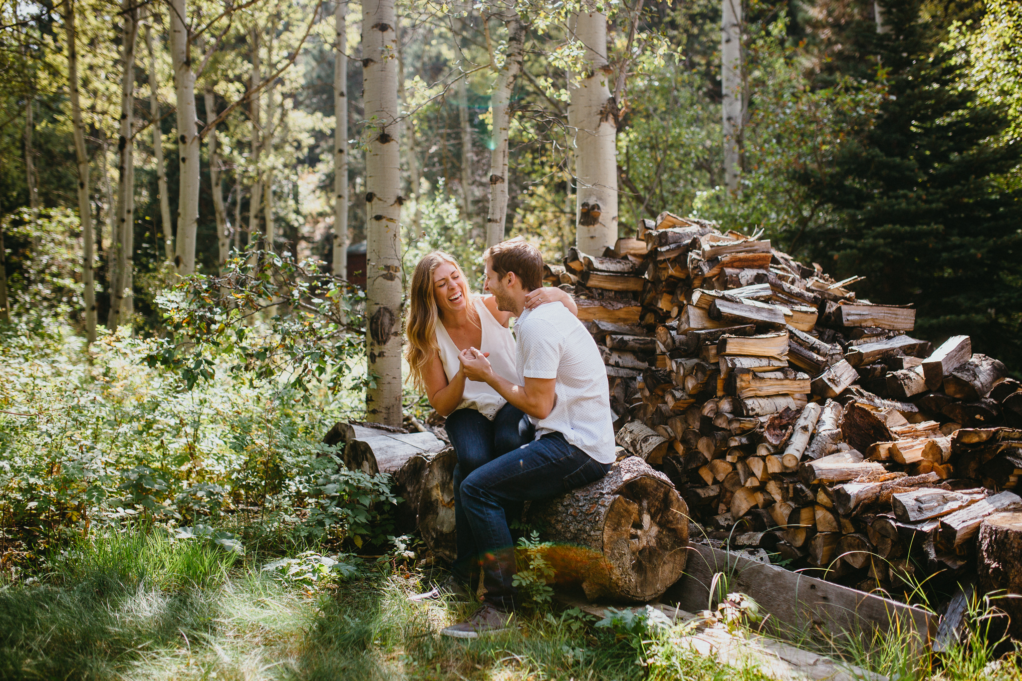 Engaged couple laughing in the woods of Colorado.