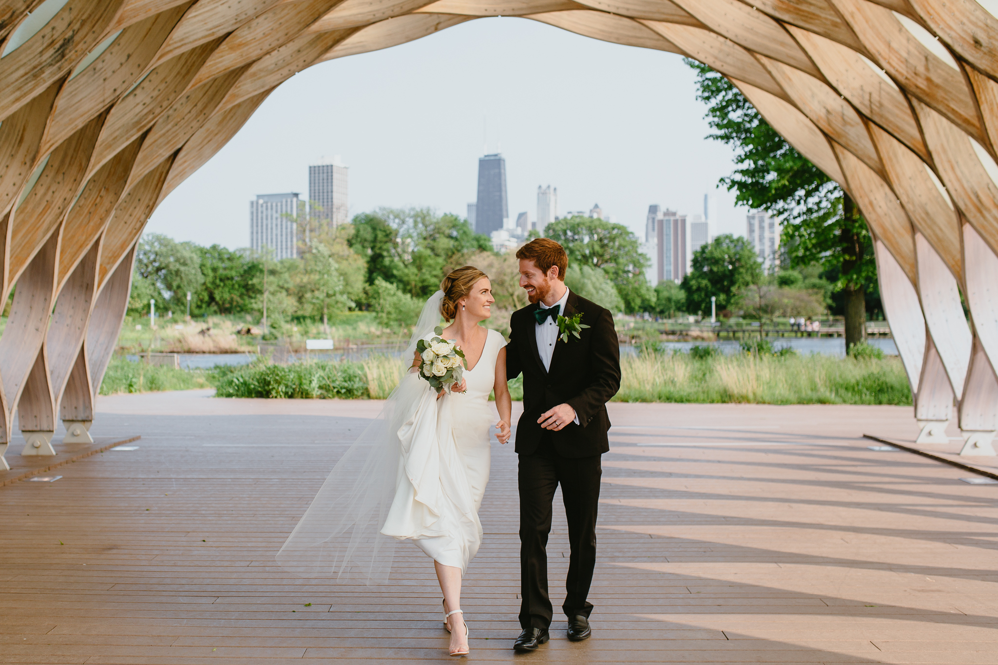Couple smiling at one another walking through Beehive Lincoln Park, Chicago wedding