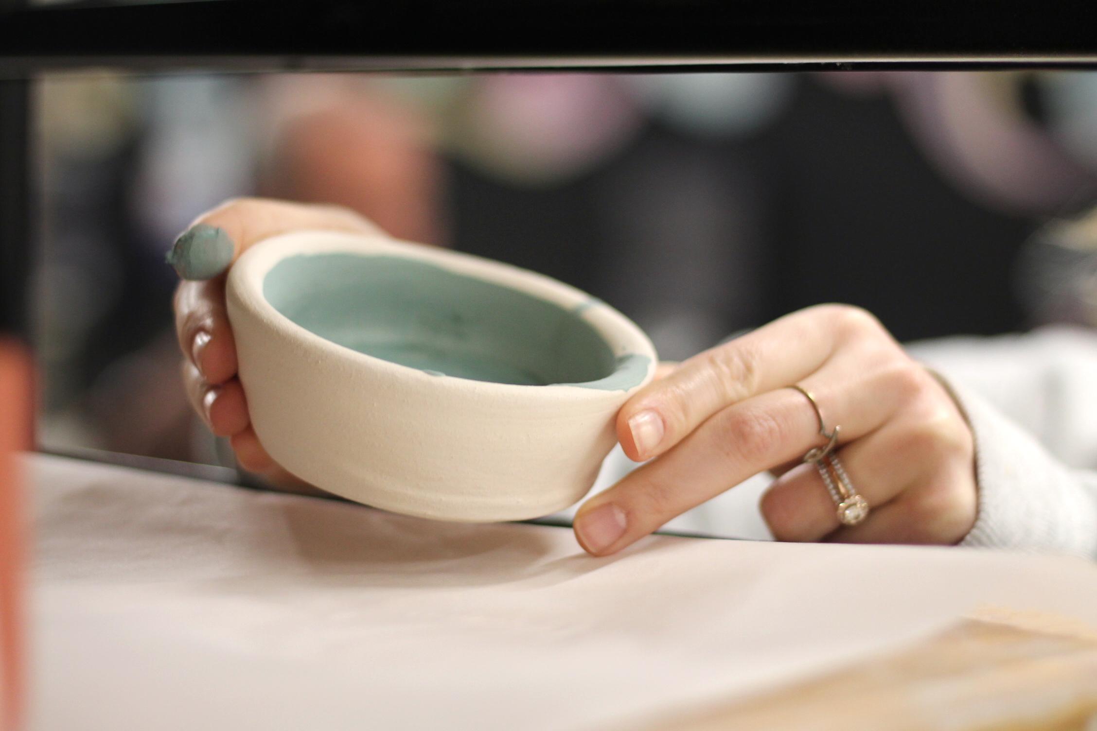 Art Lab - Pottery student putting bowl on shelf.JPG