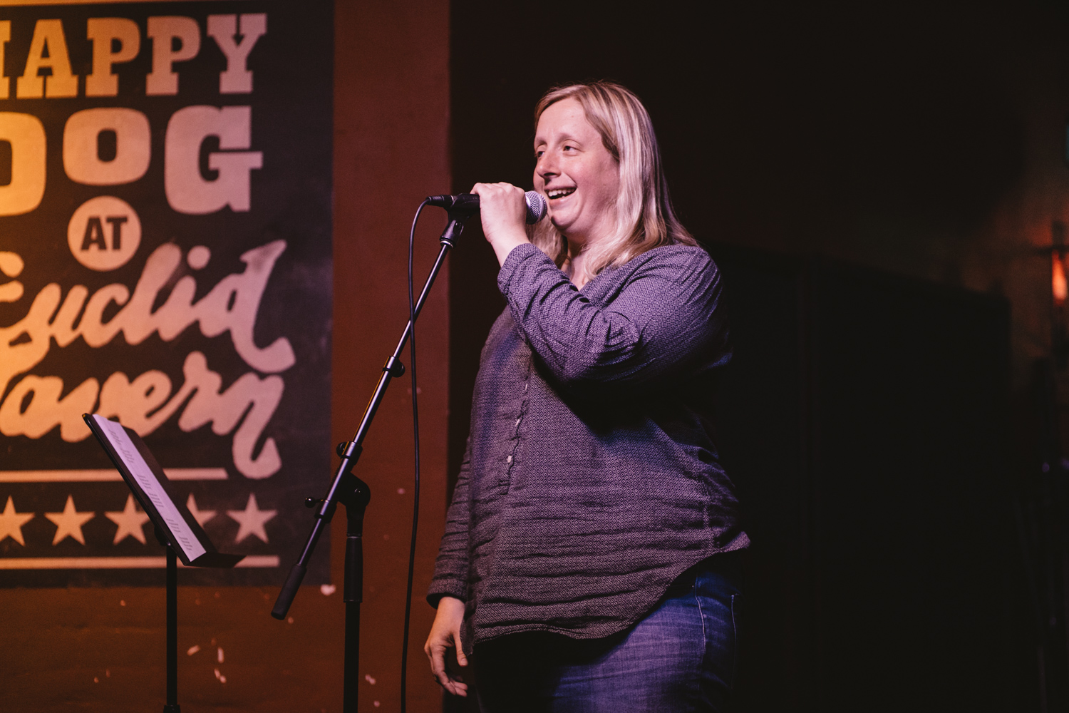 A woman smiles as she tells a story on stage at the Happy Dog in Cleveland