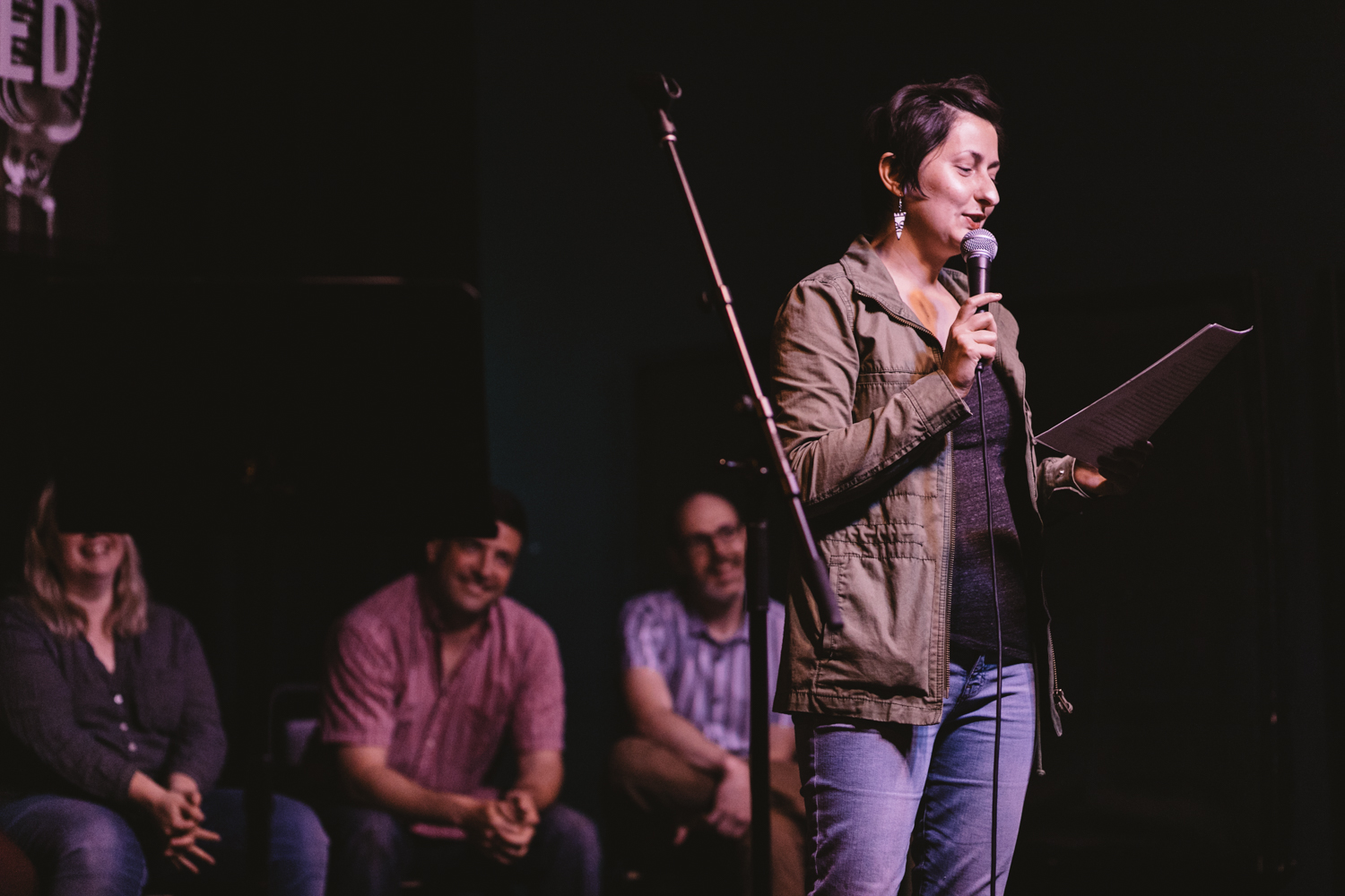 Trish DiFranco tells a story on stage with laughing people watching