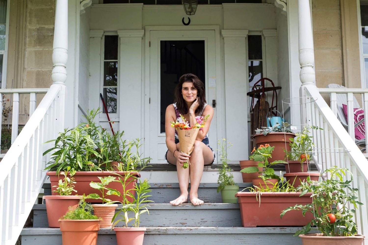Megh Wingenfeld, flower farmer, poses on her porch surrounded by containers of plants