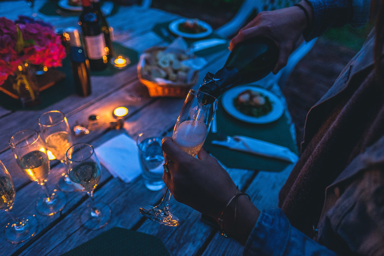 Photo of a woman pouring wine into a flute glass outside. Below her is a table filled with other glasses of wine and plates of food. The lighting is blue from nighttime, and there are warmly-colored candles scattered around the table.