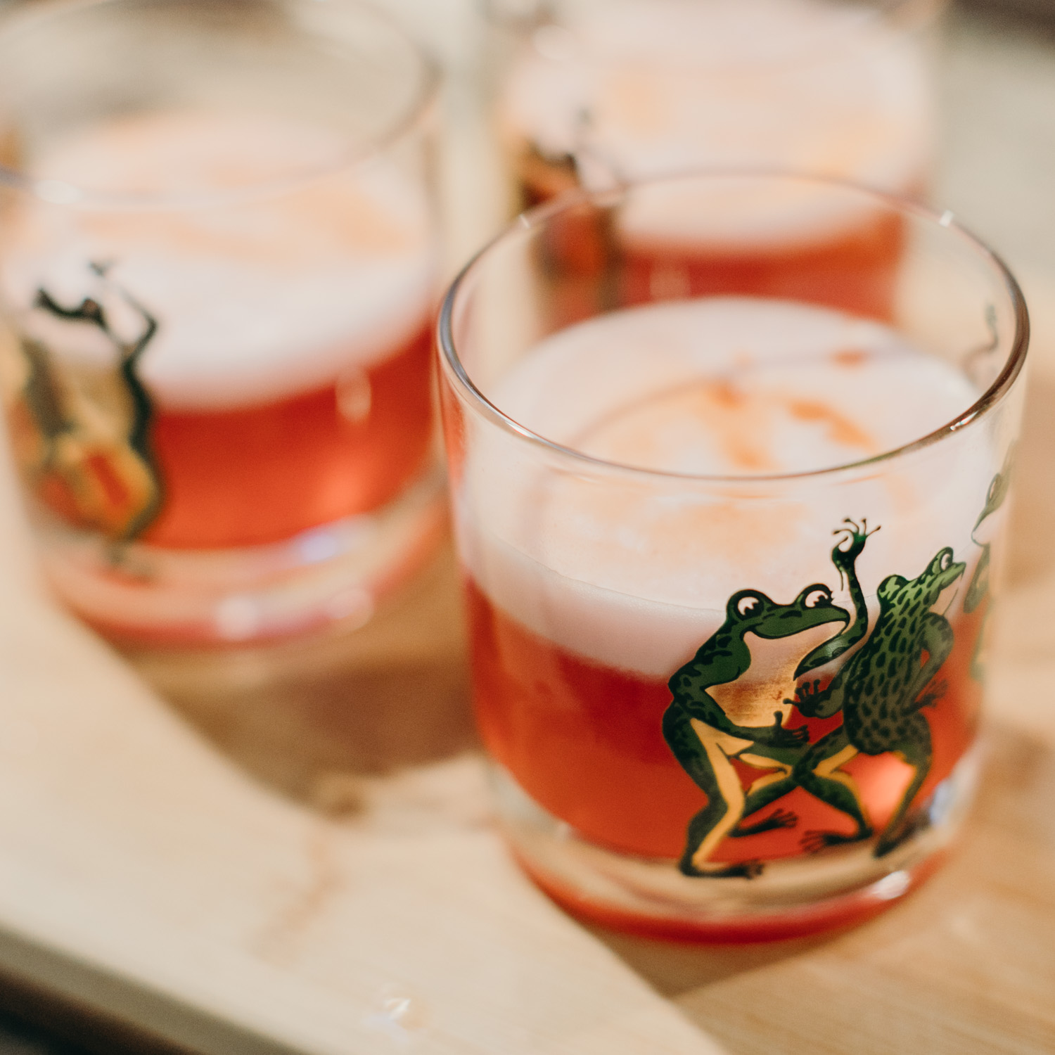 Photo of red-orange cocktails in short glasses. The glasses have dancing frogs on them.