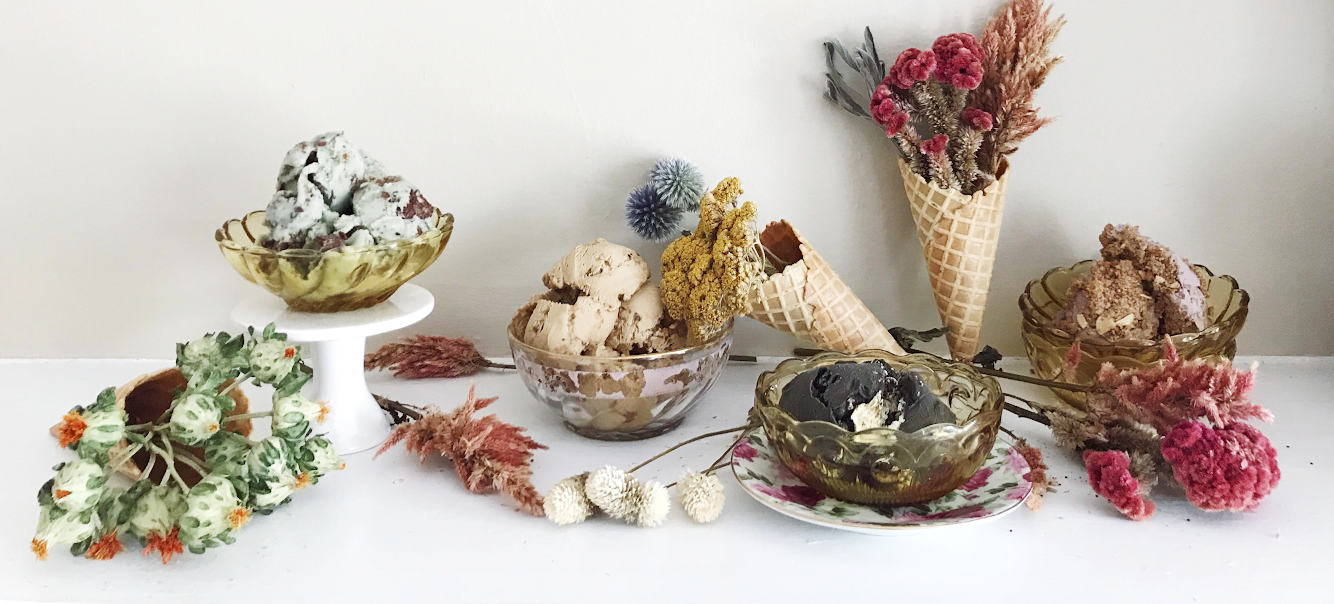 Colorful photograph of bowls of vegan ice cream, plus bouquets of dried flowers in ice cream cones.