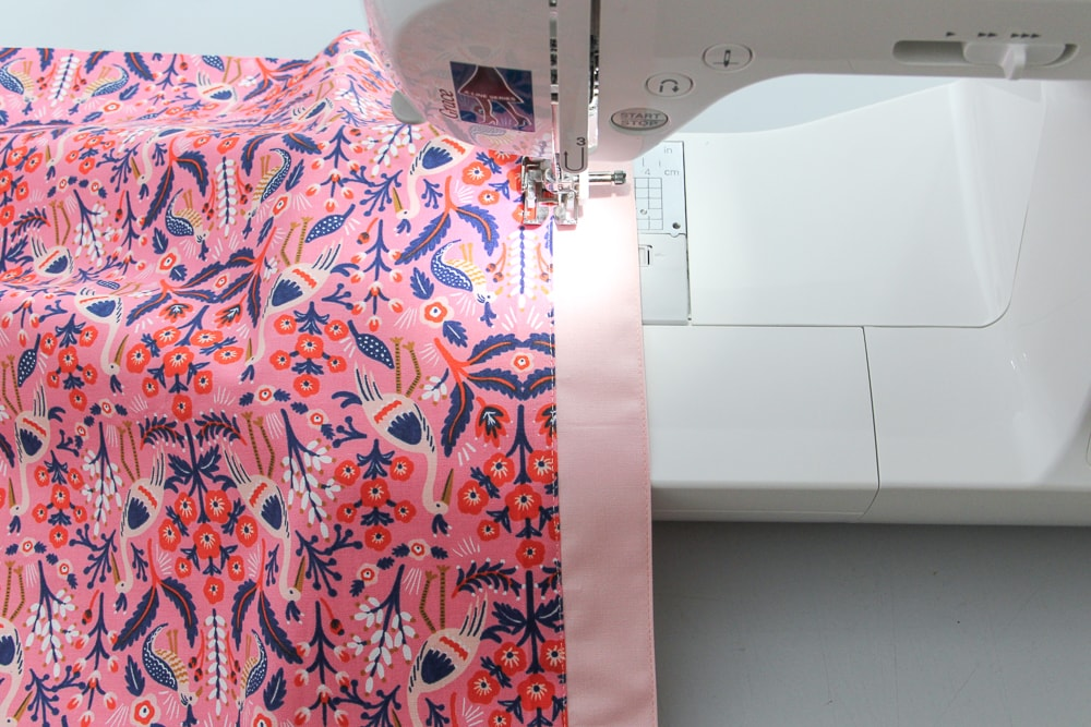 """Sew 1/8"""" from crease and along either side of the joining seam. Add a basting stitch around the 3 raw edges."""