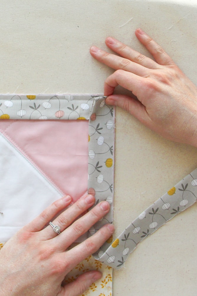 Holding up the 'triangle' that was formed by folding the binding correctly. Lay the binding tape flat and insert a pin, or several, if desired. When you start sewing again, start at the very edge, backstitching at the start.