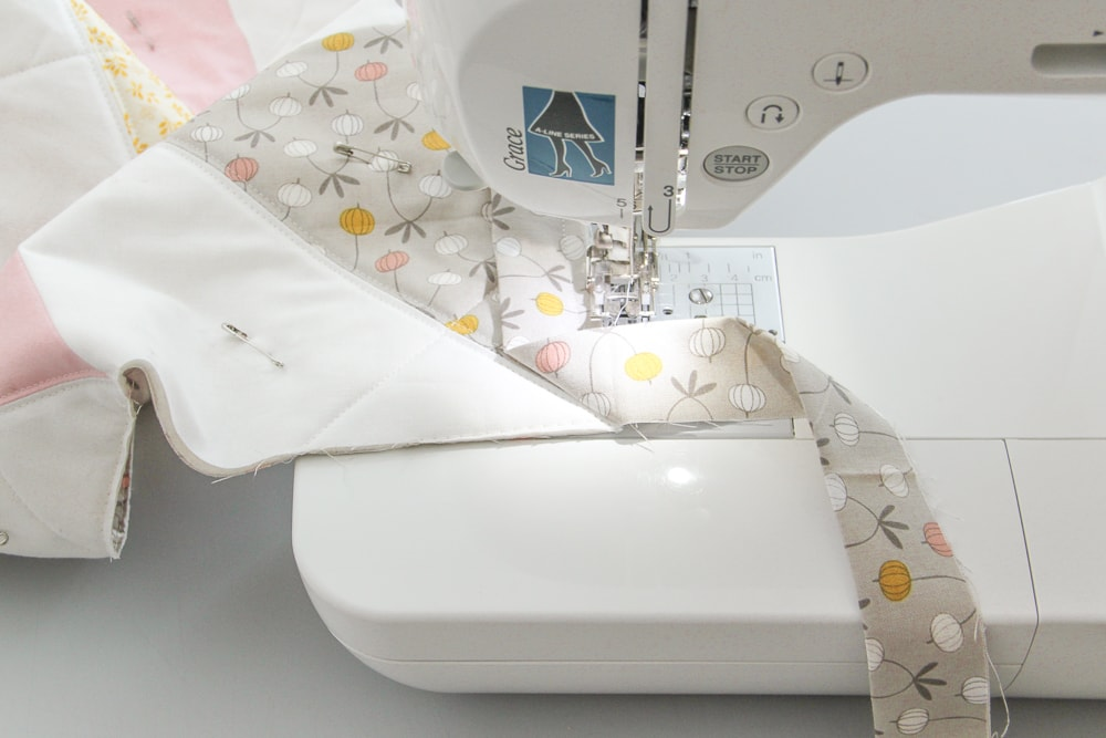 """Stop sewing with 1/4"""" left and backstitch to secure. Without cutting threads, lift your presser foot and needle, create the 45-degree angle fold with the binding, working near the sewing machine."""