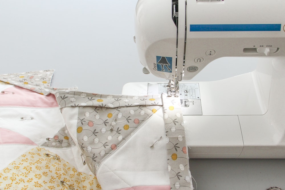 With the binding aligned to the adjacent edges, lay flat and start sewing again from the quilt edge, backstitching to secure the stitches. You'll have a few loose loops from the thread remaining connected, but these will get tucked inside the binding at the finish of the quilt.