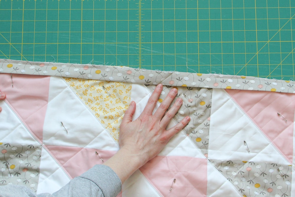 6. Fold the connected binding in half and align the raw edges with the edge of the quilt.