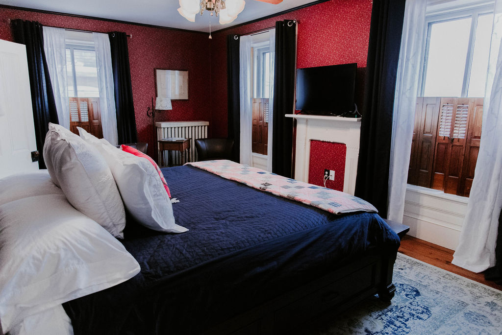 Motter guest room with king bed and red wallpaper