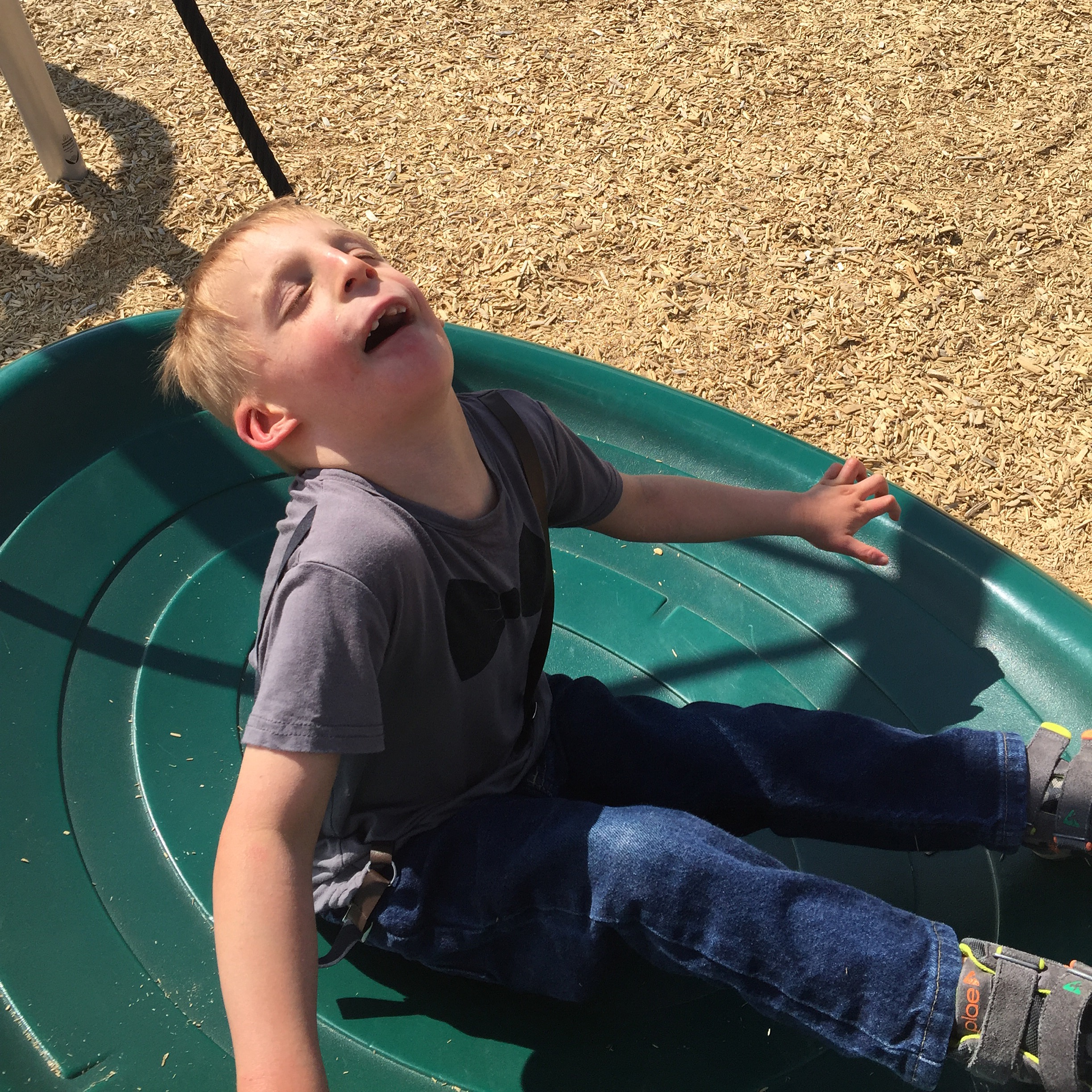 Atticus, summer 2016, laughing as he swings at the park.