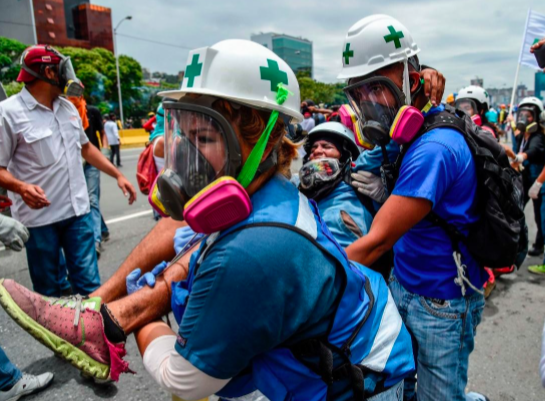 An anti-government demonstrator, wounded during clashes with the police, was carried away by Green Cross volunteers in Caracas on May 3.CreditJuan Barreto/Agence France-Presse — Getty Images