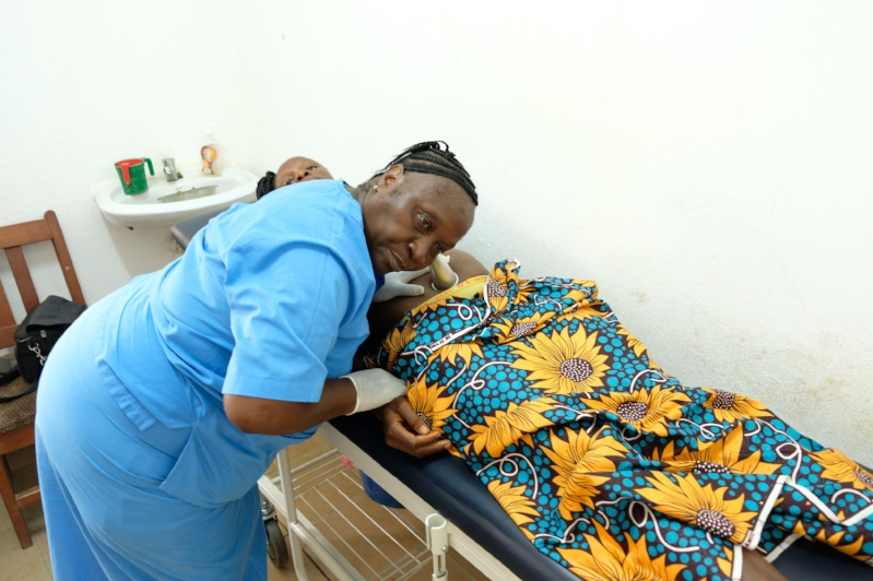A Traditional Birth Attendant (TBA) measures the heart rate of her patient's unborn baby during Antenatal Class (ANC), at Wellbody Clinic, Kono, Sierra Leone.
