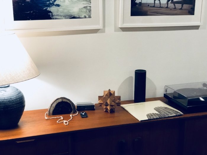 Pictured: Pure Genius Acorn, next to a lamp, geode, and vinyl record player on a living room cabinet.