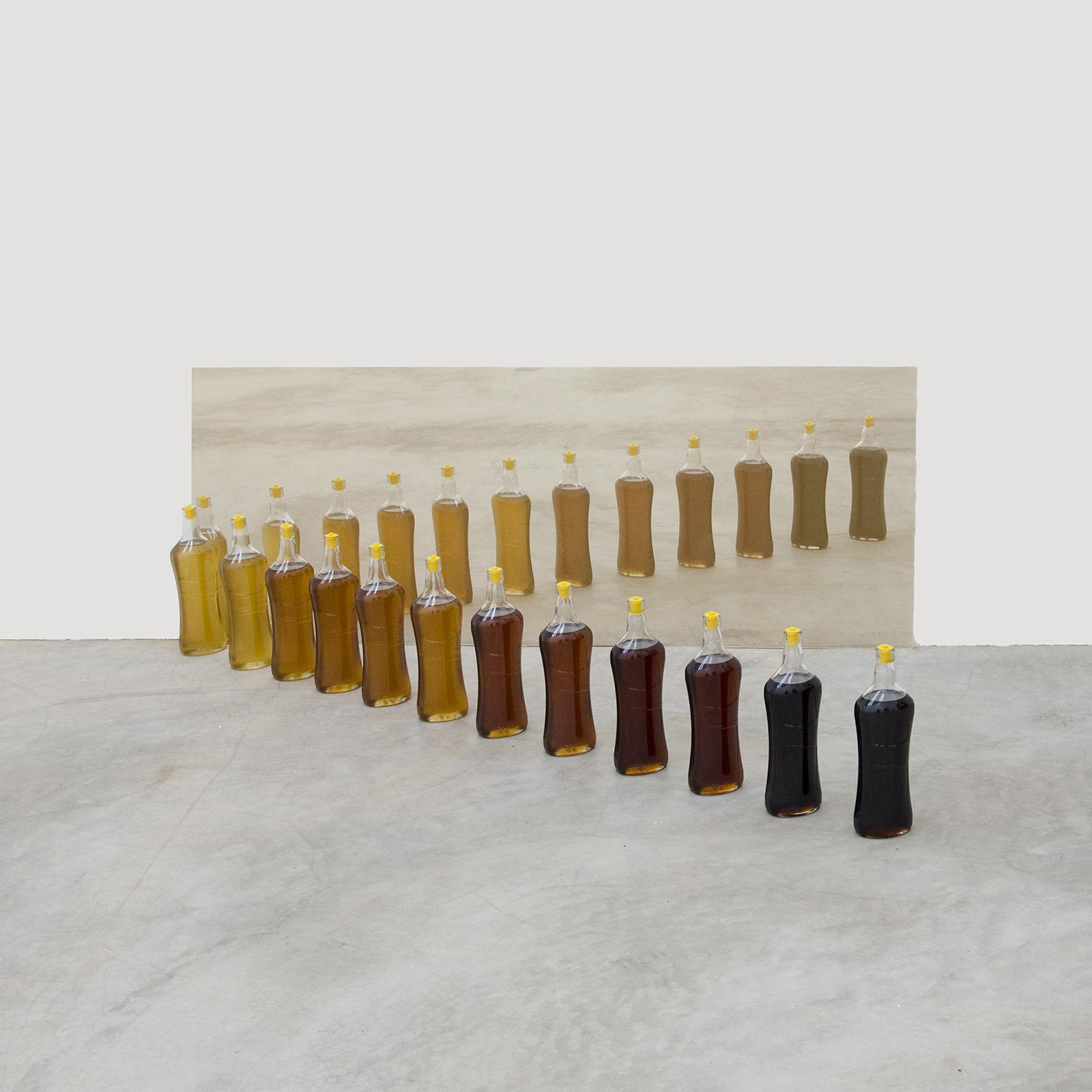 melzinho,  2019  garrafas de vidro, mel e vidro dourado  60 x 170 x 80 cm