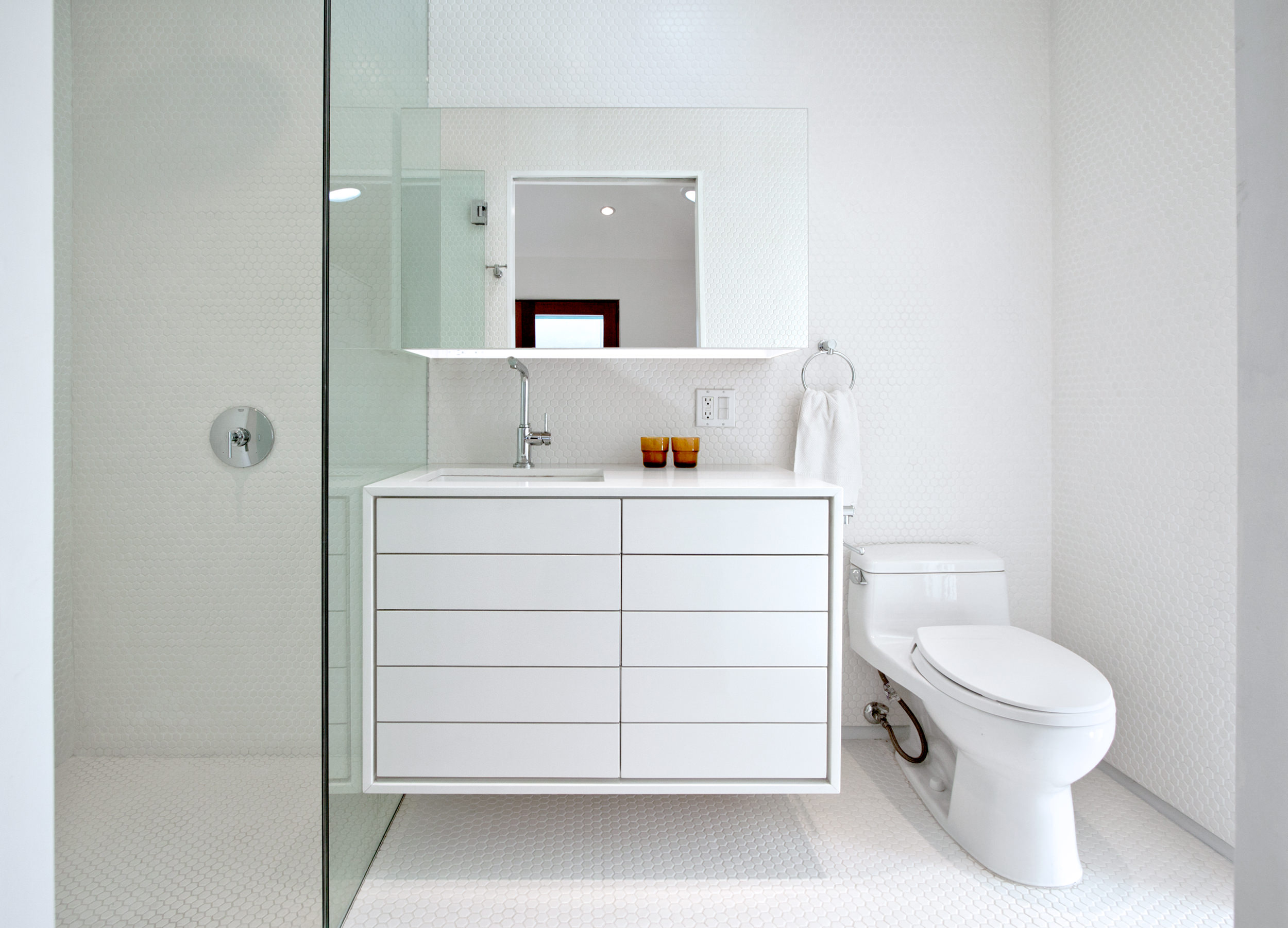 View of the bathroom with the wall-mounted vanity and curbless shower.