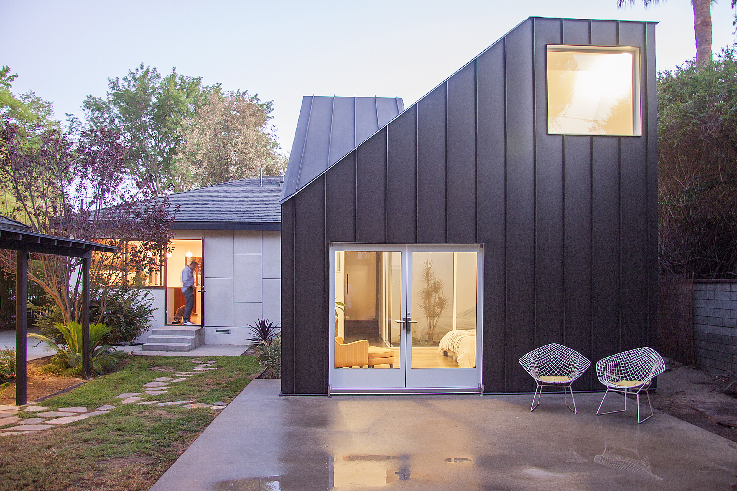 The exterior of the addition is clad in a dark standing seam metal that is continuous from the roof to the facade.