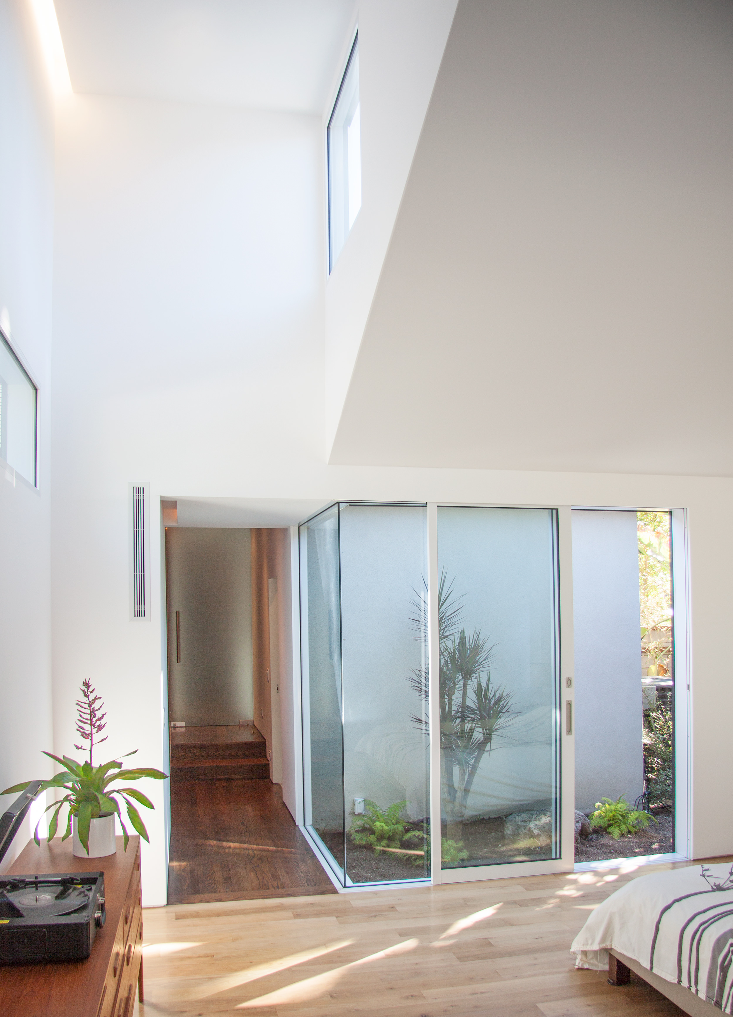 """View of the hall through the """"core"""" that separates the bedrooms from the more public areas of the house."""