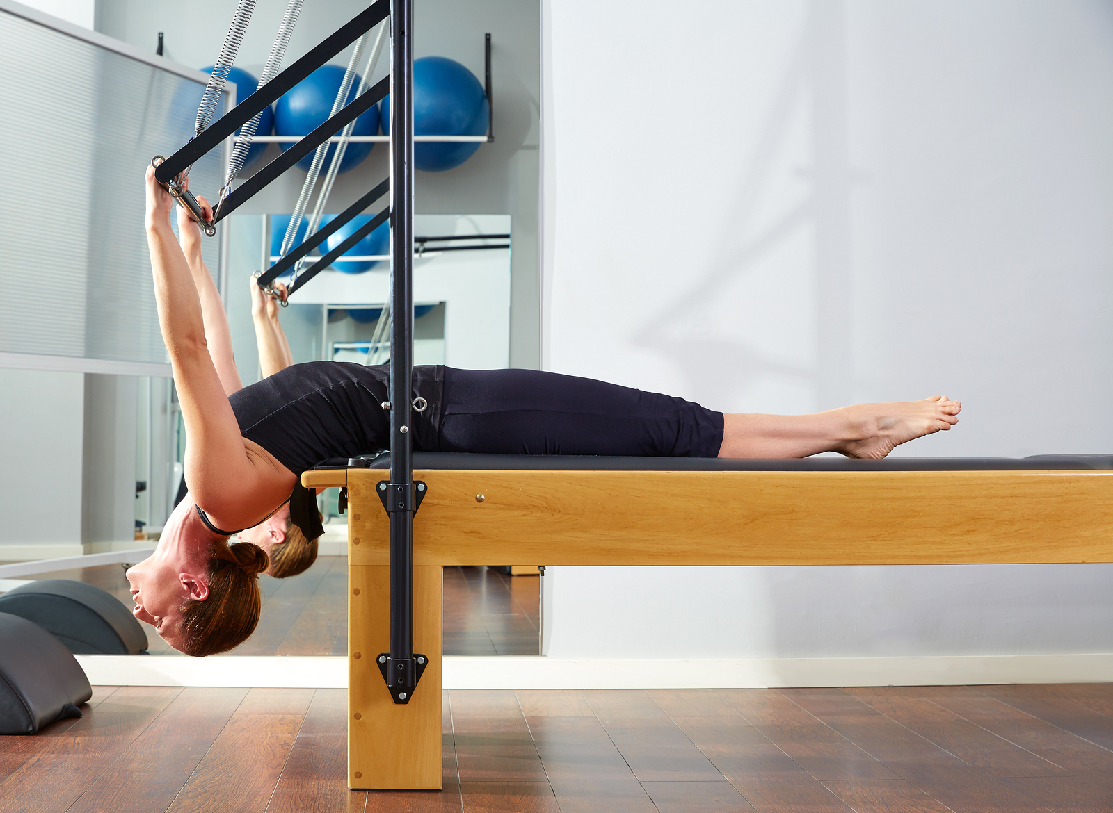 A young healthy woman stretches out here back using pilates equipment, with her head leading the tilt.