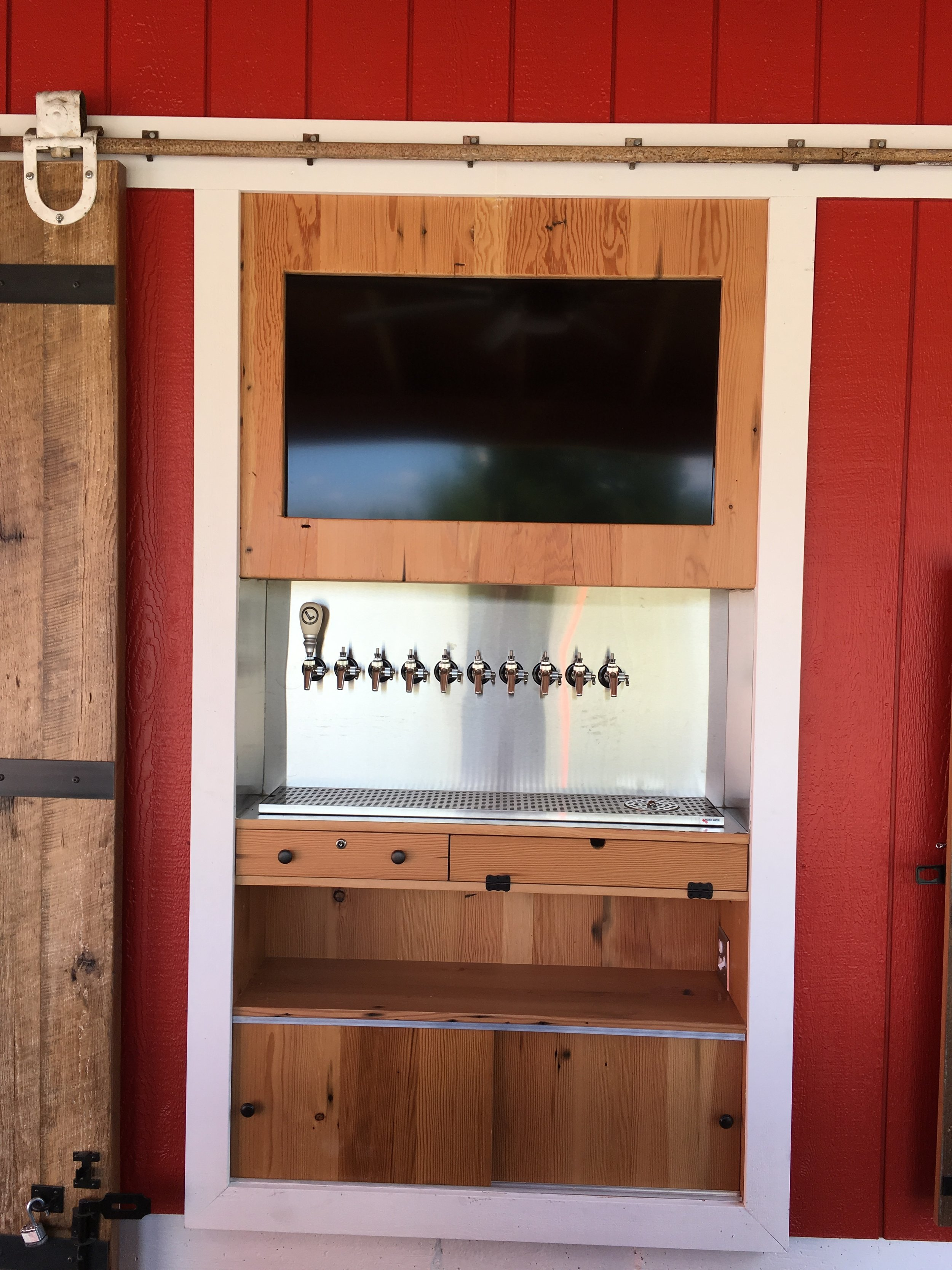 Tv, taps, and shelves on back bar