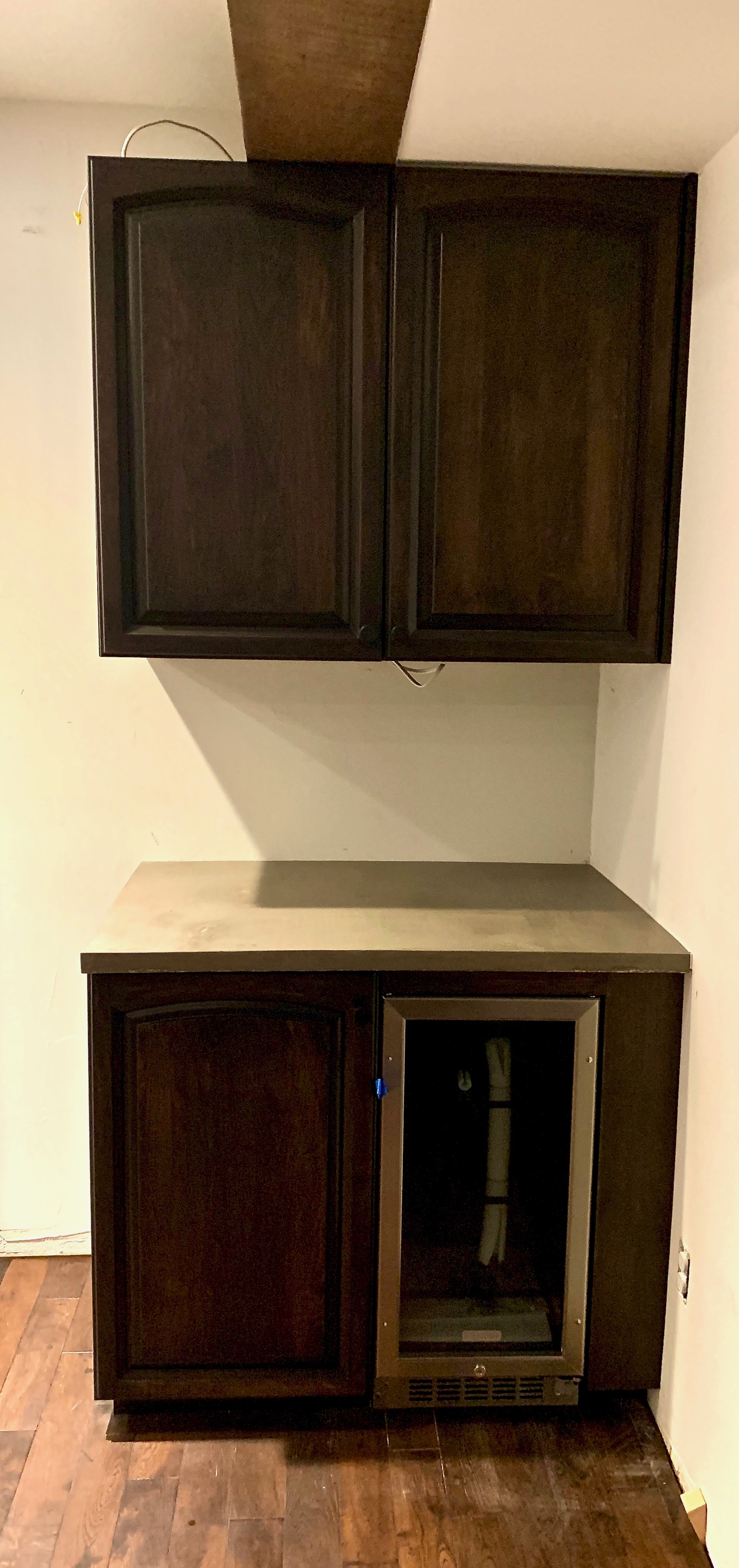 Cabinets with concrete countertops and built in fridge.