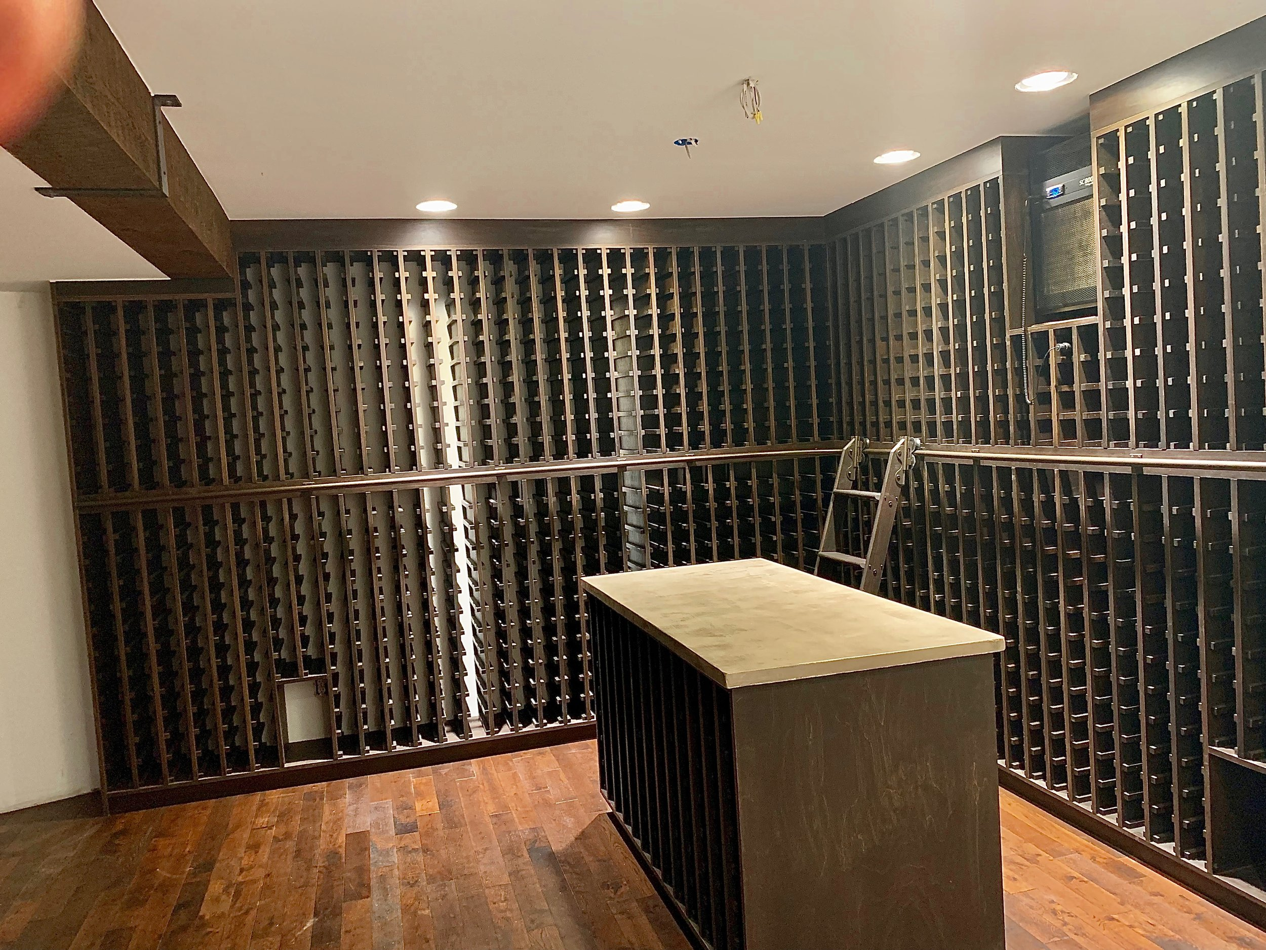 Wine cellar with concrete countertops and faux wood beam.