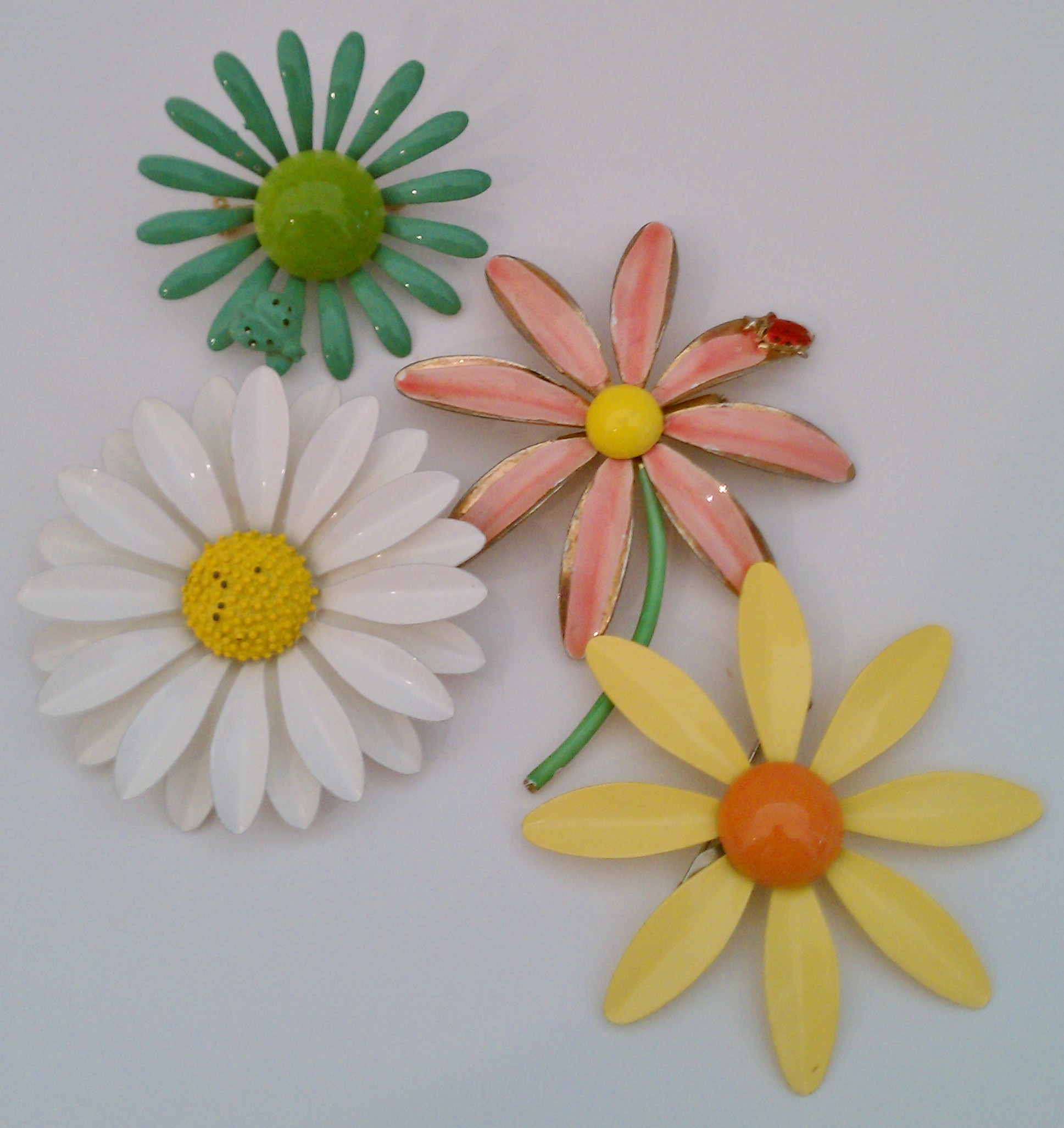 Enameled flower pins were very popular in the 1950s and I think they may be making a come back.  The yellow and aqua daisies belonged to my mother and the pink and white pins were mine.
