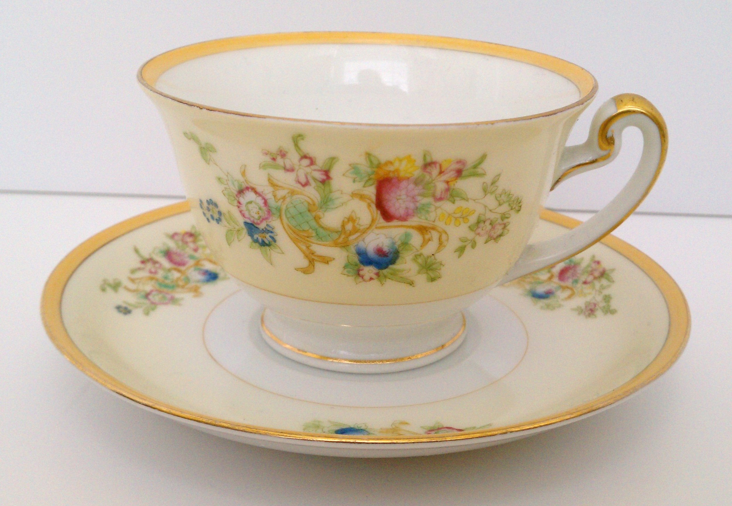 Meito China cup and saucer made in Japan ... pale yellow and white with floral motif and heavy gold trim