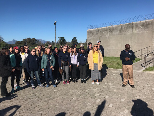 """Robben Island: Choristers sing """"Long Walk to Freedom"""" to their tour guide, former political prisoner imprisoned there. Photo: Anita Gay"""