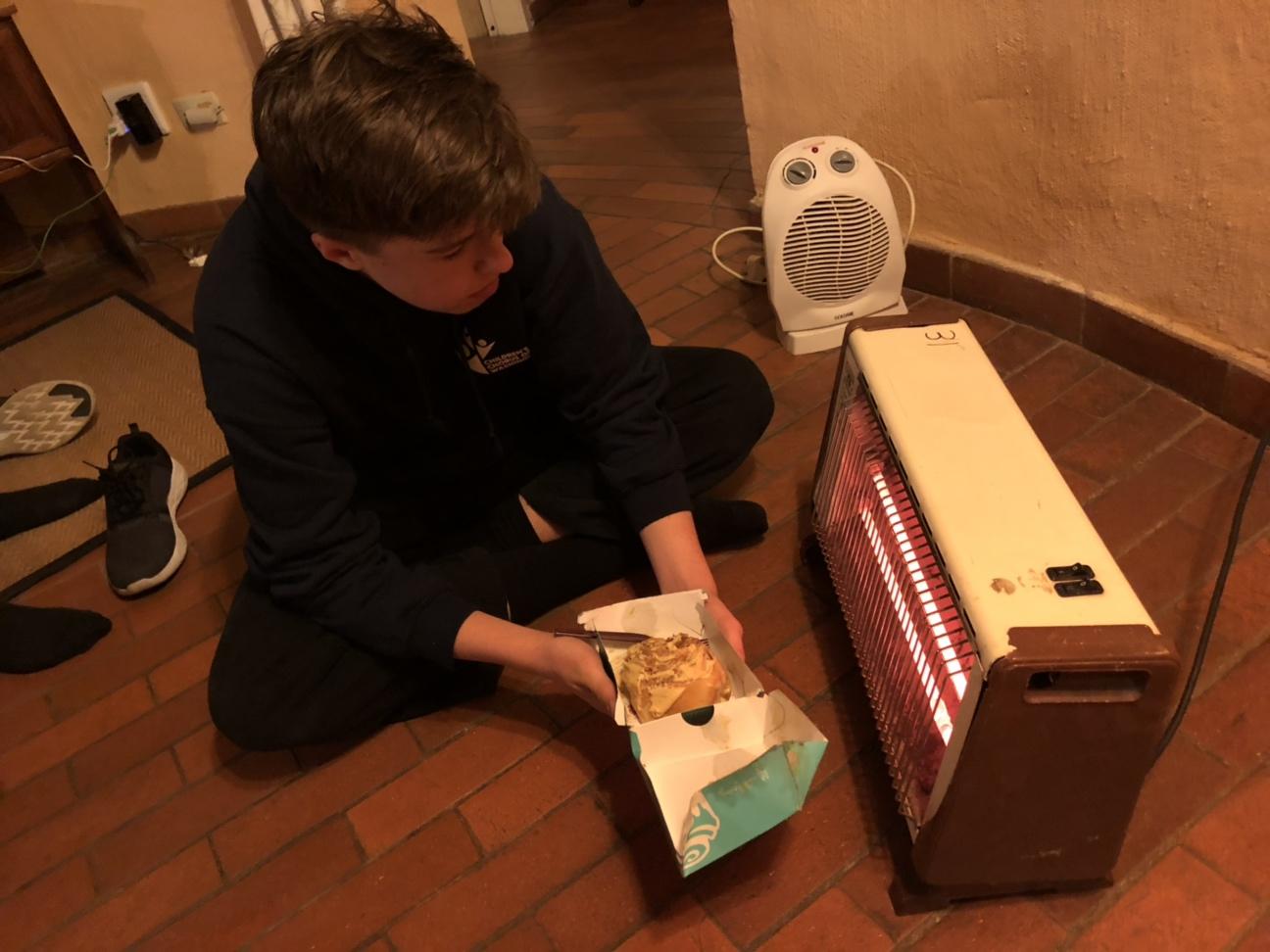Jack heating his Cinnabon by the space heater. Photo: Sam Mencimer
