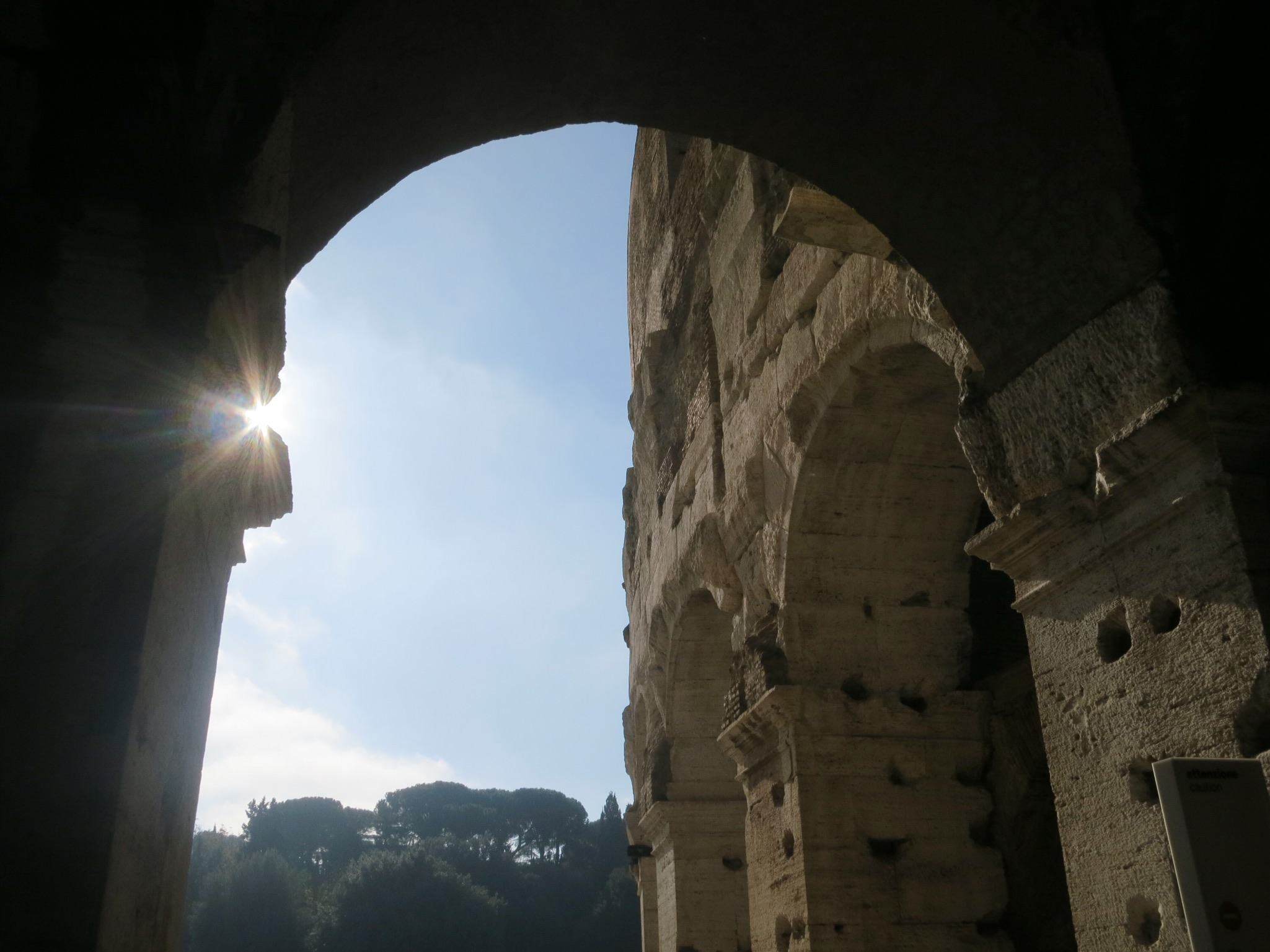 Arches frame beautiful views of the city throughout the Colosseum in Rome, Italy.
