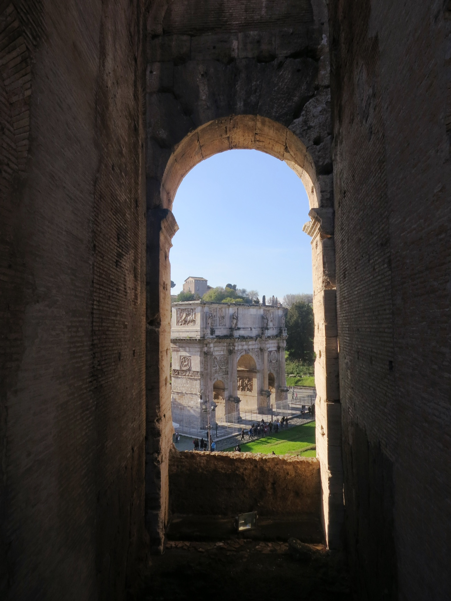 An arch in the Colosseum frames the Arch of Constantine in Rome, Italy.