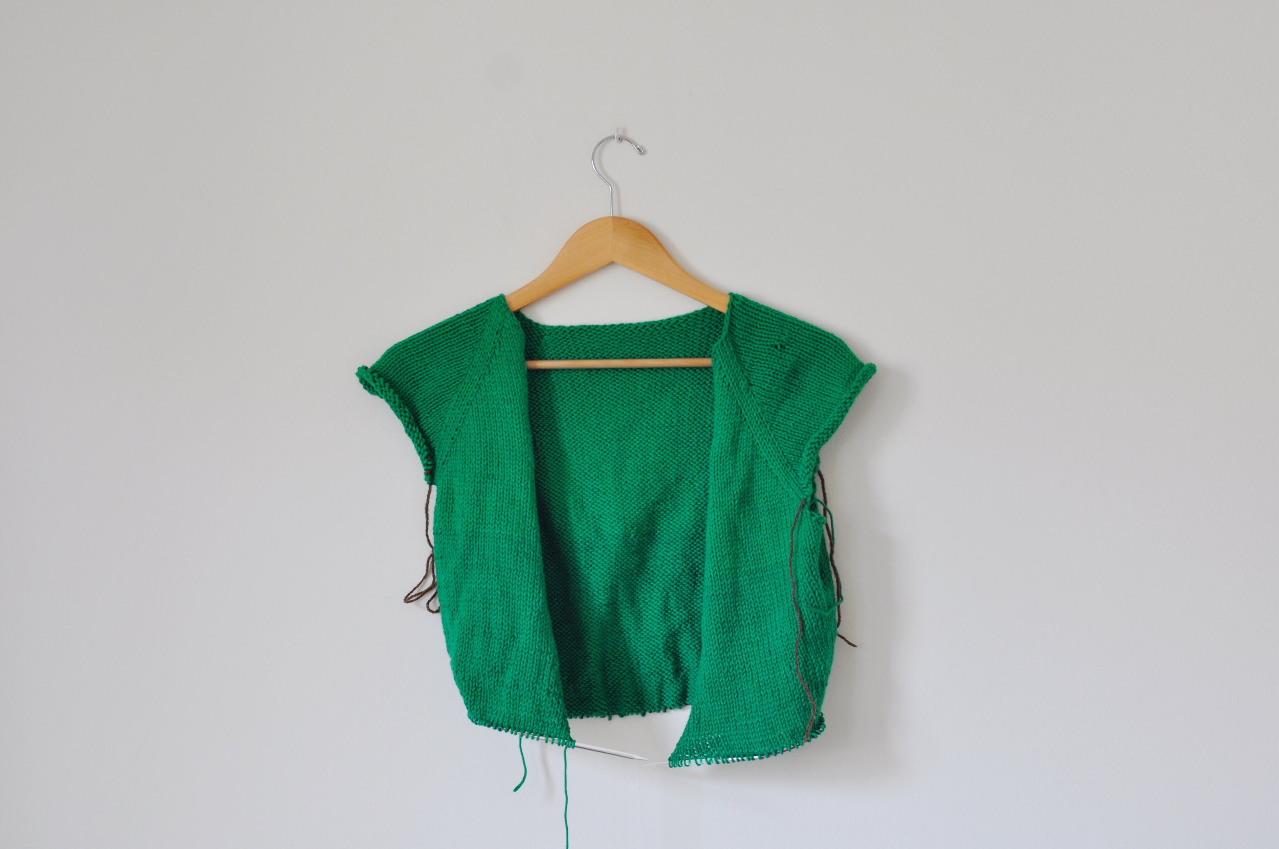 Green cardigan sweater knitting in progress