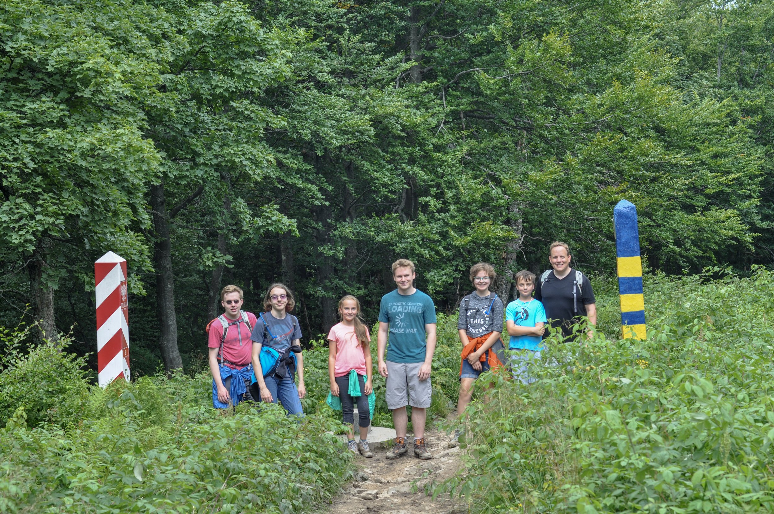 Hikers between the Polish and Ukrainian border markers on the Tri-border Hike in the Bieszcady Mountains