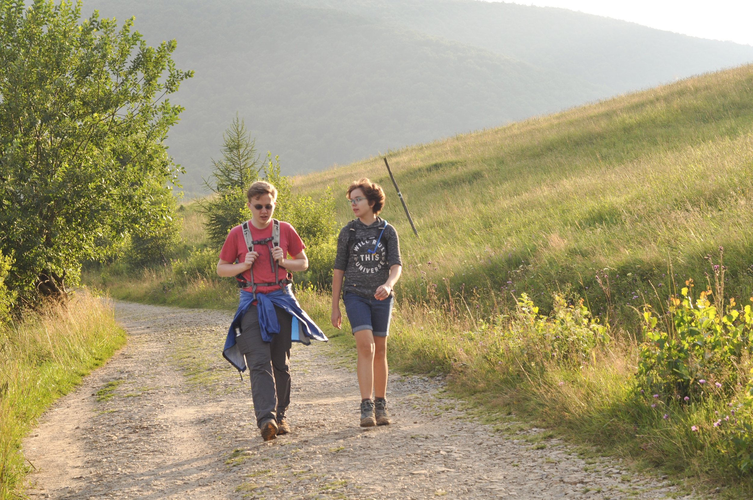 Two hikers walking on a gravel road as the sunsets at the end of the Tri-Border hike in the Bieszcady Mountains