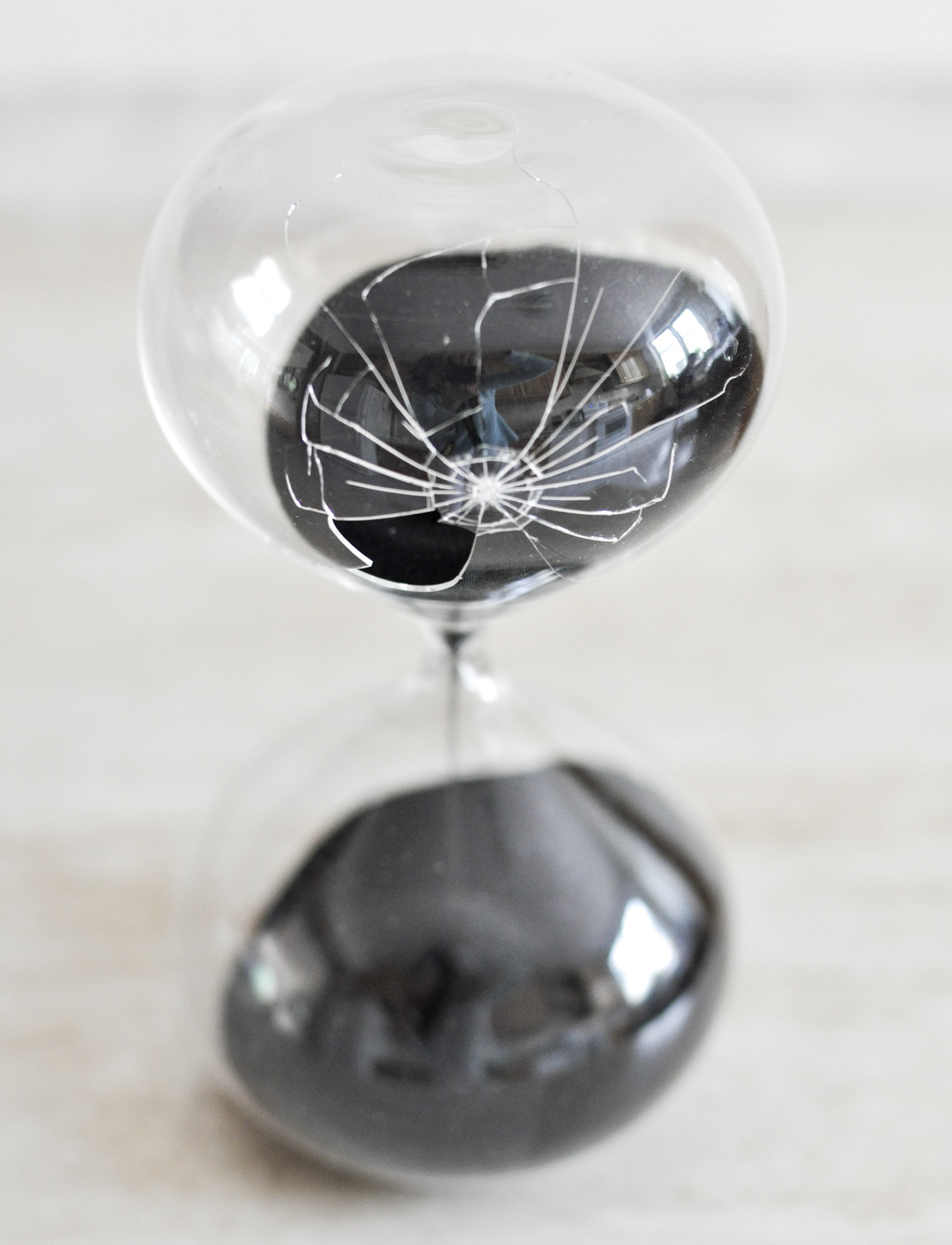 Glass sand timer with black sand and a shattered bulb