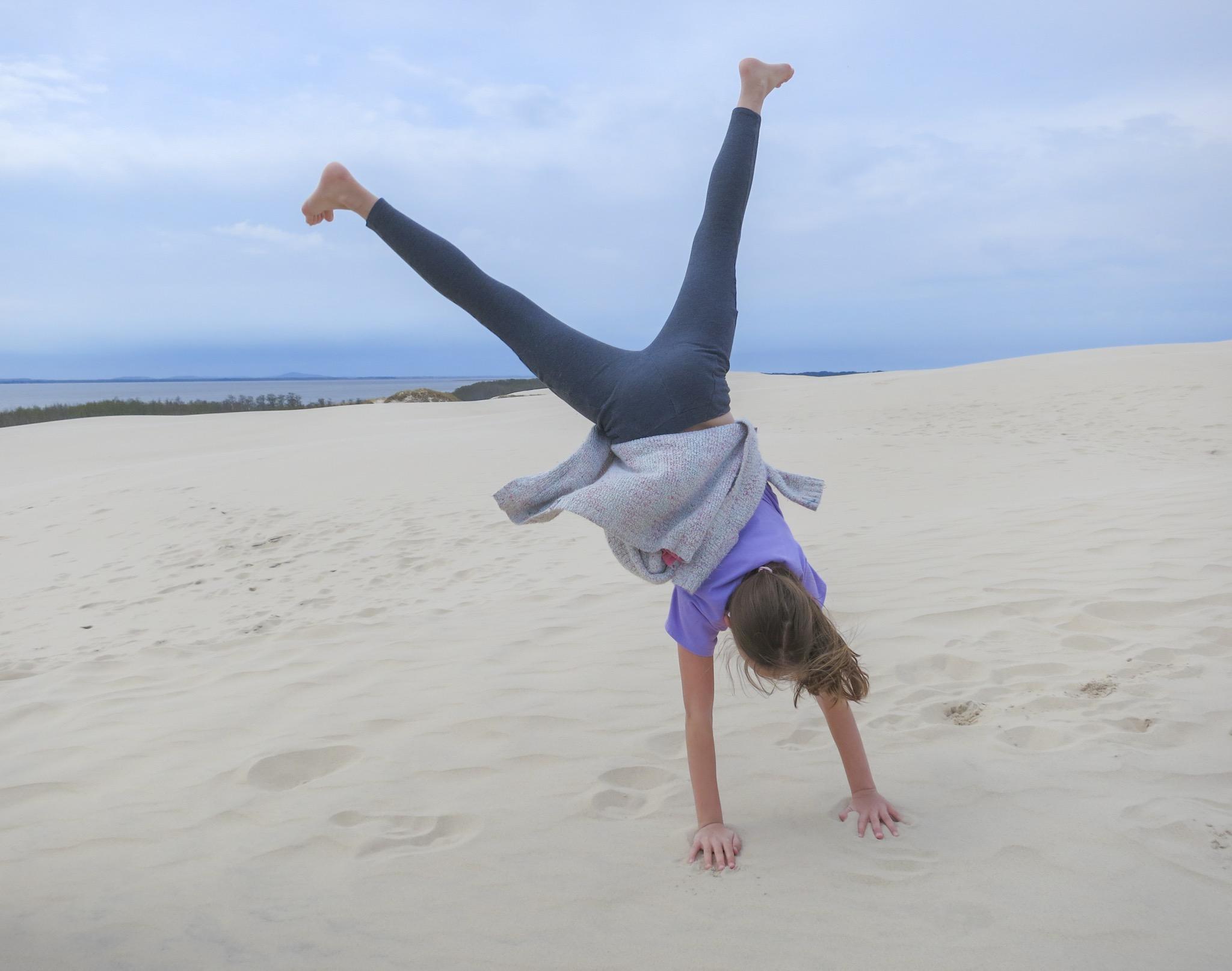 A girl does a cartwheel on the Łackca Sand Dune In Słowiński National Park