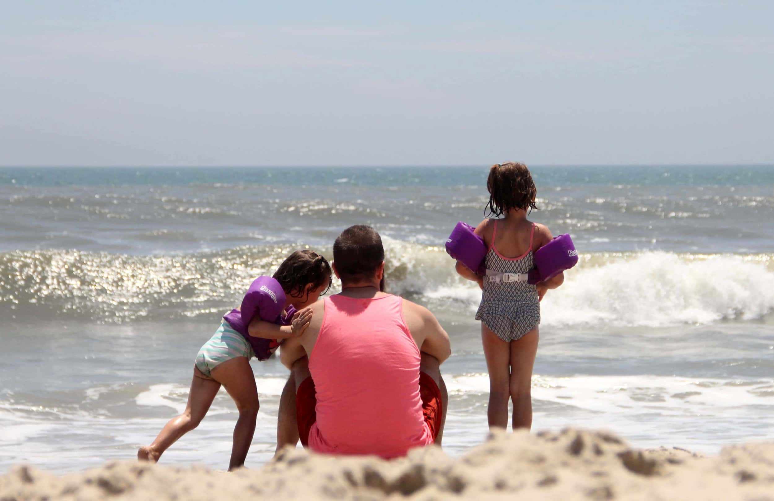A dad and his daughters watching the Atlantic waves crashing on the Assateague beach.