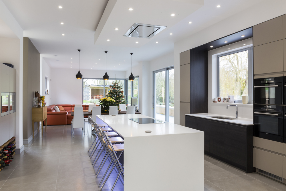 Central Island - The central island at this Cambridgeshire new build is one of the focal points of the kitchen. The island is minimal with the stone worktop wrapping down each side providing seating for four people.Island breakfast bars are often a key component of kitchens and the place where family and friends congregate.