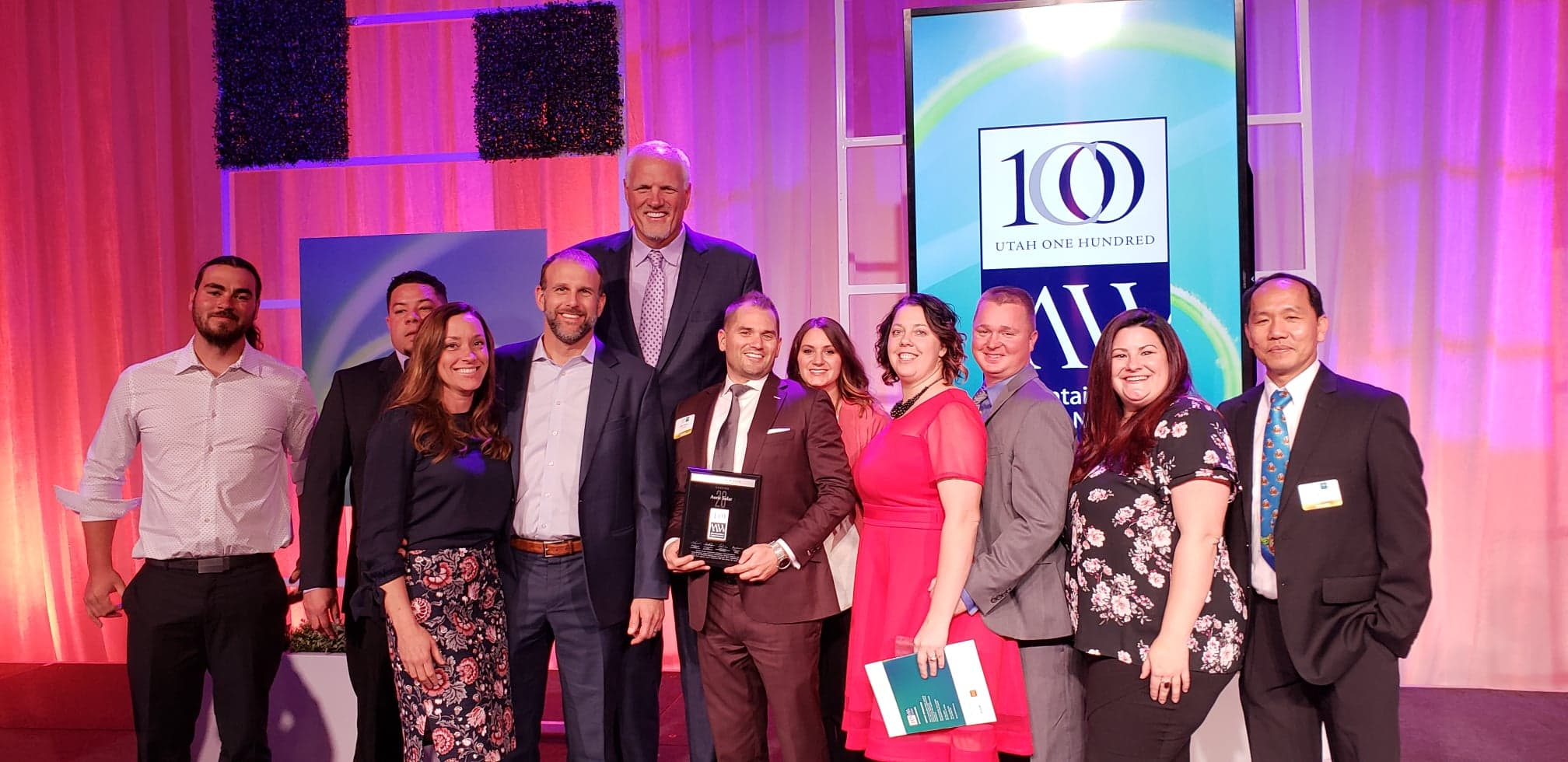 A group of Auric colleagues with the award presented by Mark Eaton, former NBA basketball player for the Utah Jazz.