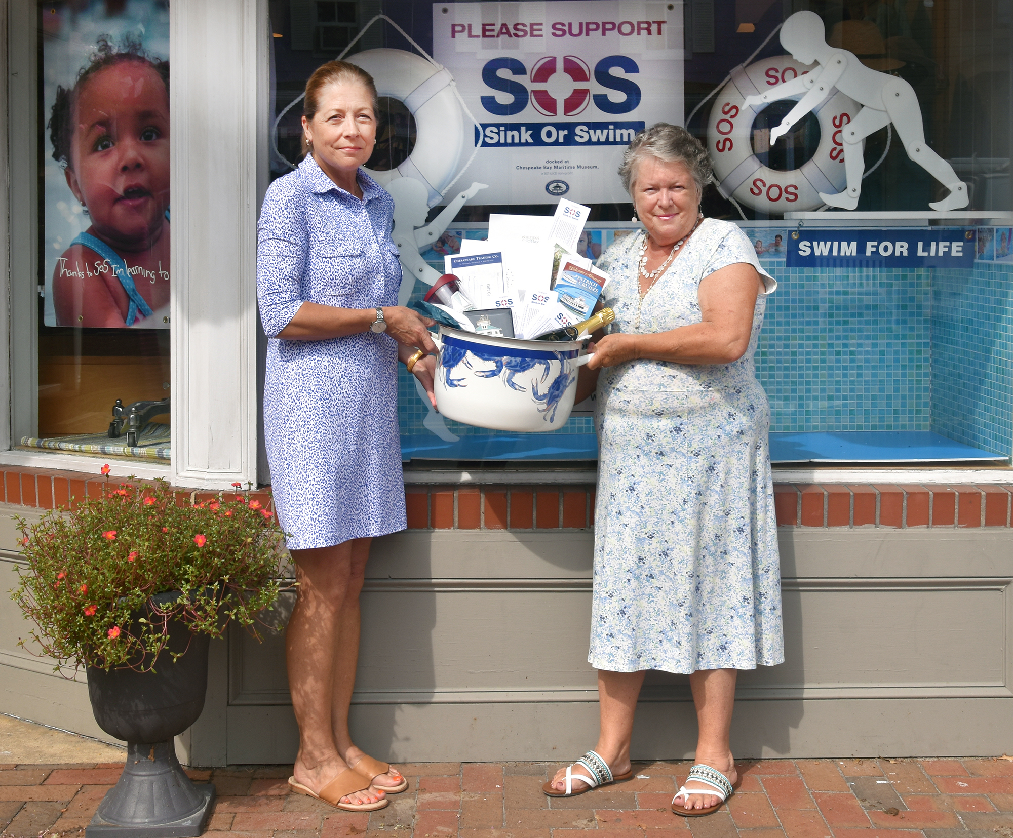 Jo Batters, left, is presented with raffle prizes by Chesapeake Trading Company owner Lynda Boettner. Chesapeake Trading Company hosted the SOS Sink or Swim raffle again this year, dedicating window space throughout the summer to help showcase SOS's mission of teaching children to swim and be safe in the water. To learn more, visit sossinkorswim.org.