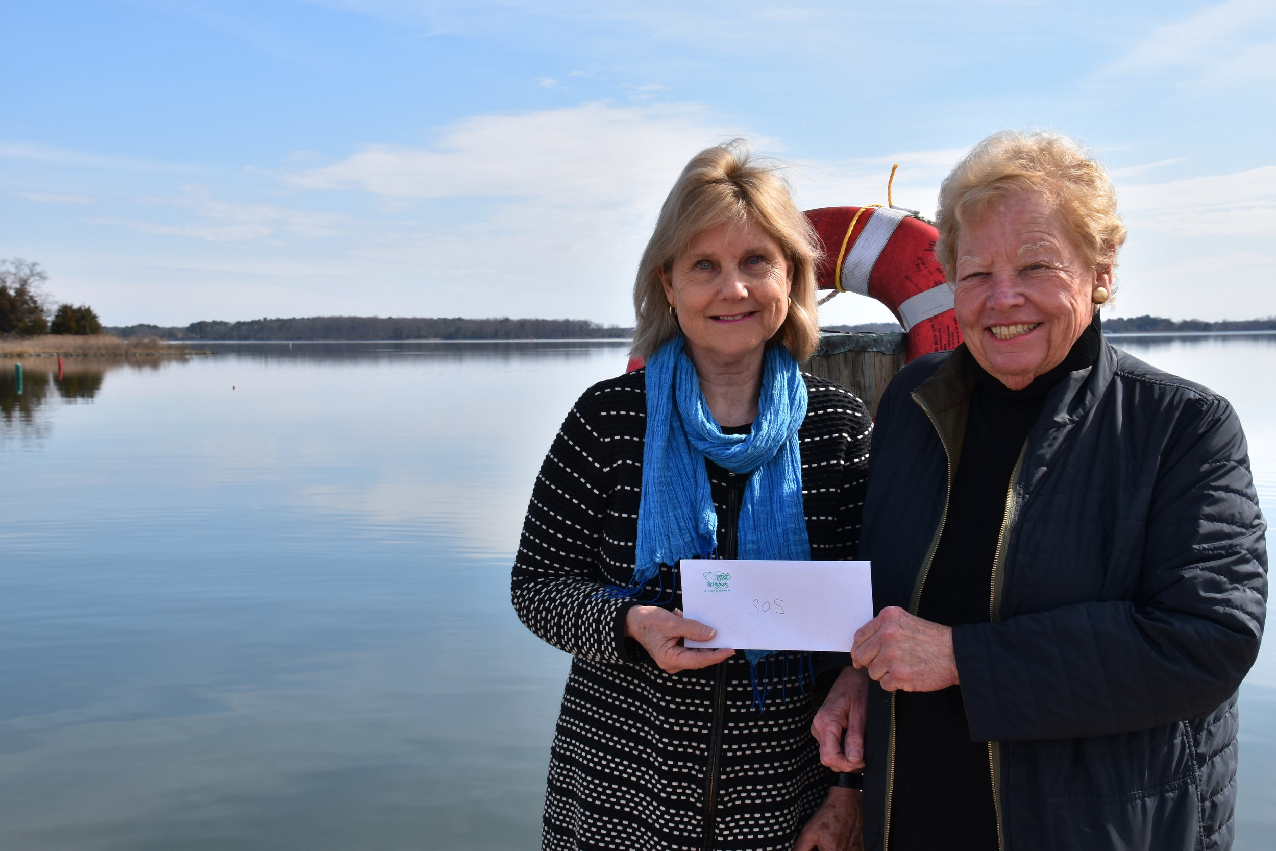 From left: Christmas in St. Michaels Treasurer Linda Seemans with SOS Sink or Swim Council President Libby Moose accepting a check from Christmas in St. Michaels in support of the children and adults served by SOS's free, two-week swimming lessons offered at Talbot County's community pools. To support a swimmer or to learn more, go to  sossinkorswim.org.