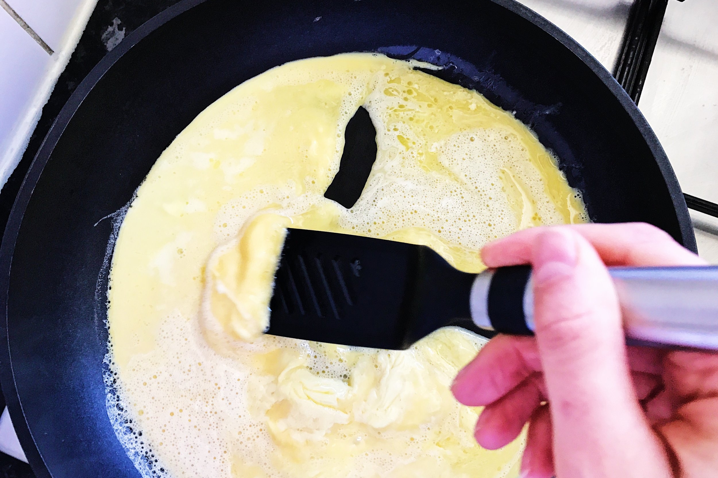 Continue stirring, careful not to break up large curds and pushing the eggs from one side of the pan towards the middle and to another side. Eggs that are still raw will fill up empty spots of the pan.