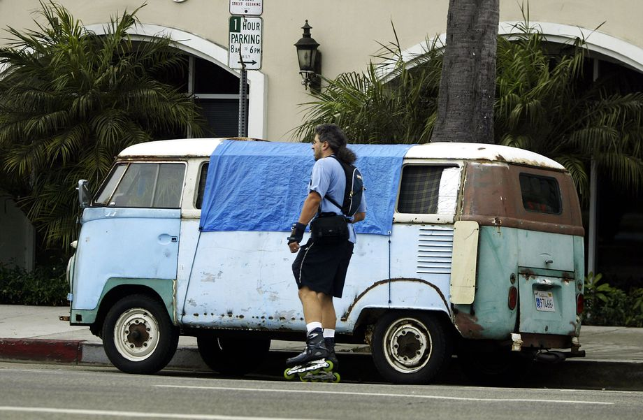 A skater passes a van where a homeless person is sleeping in Venice.  Photo by David McNew/Getty Images