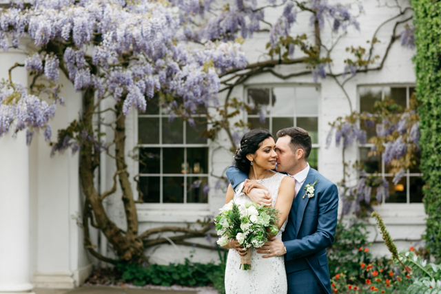Bride and groom agains Wisteria.jpg