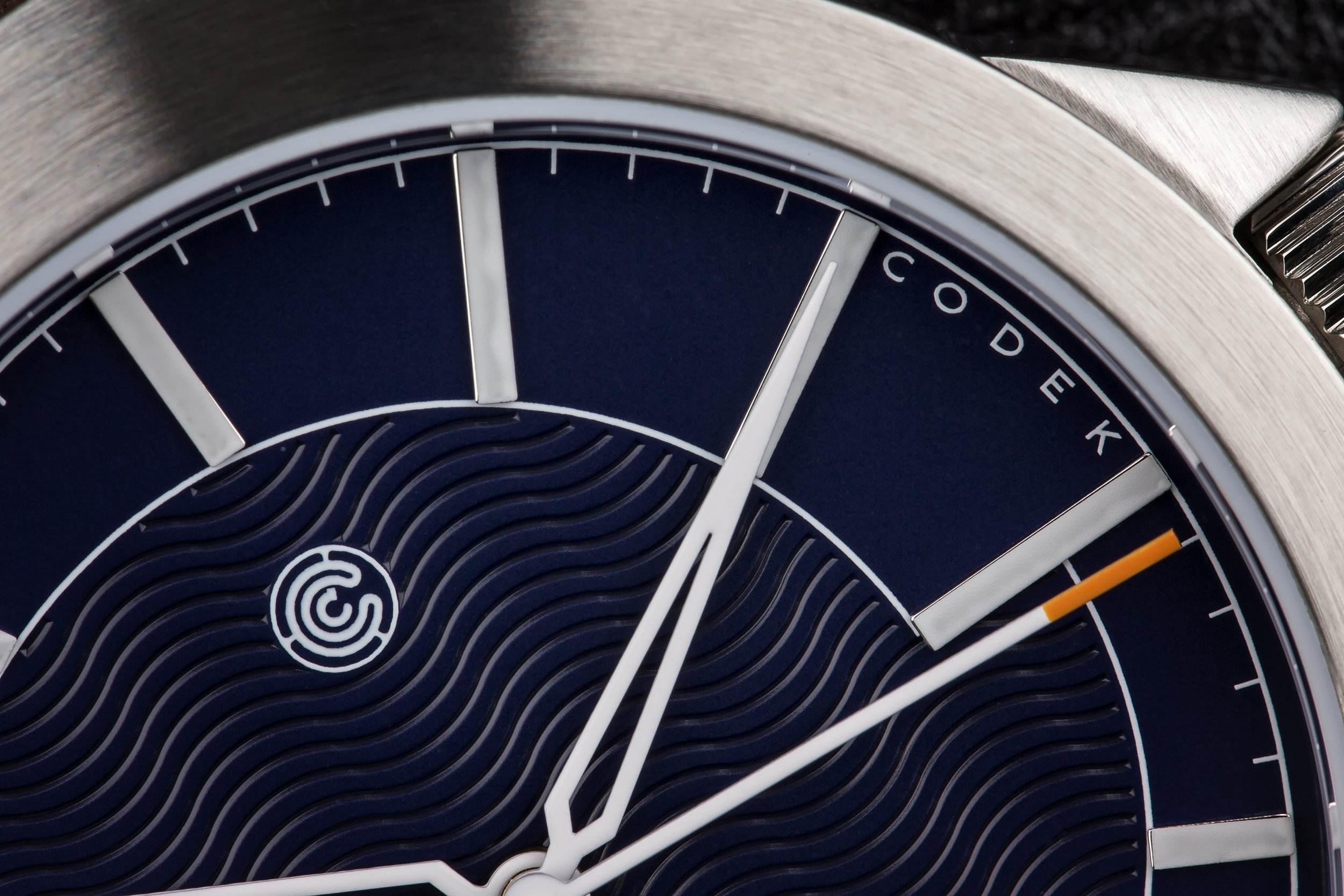 Dial - The hour indices add playful tension because they do not conform to one standard length. The embossed waves shimmer in different lighting — at times blending into the background, and at other times forming the highlight of the dial. Design elements like these keep the watch fresh and visually interesting over time.