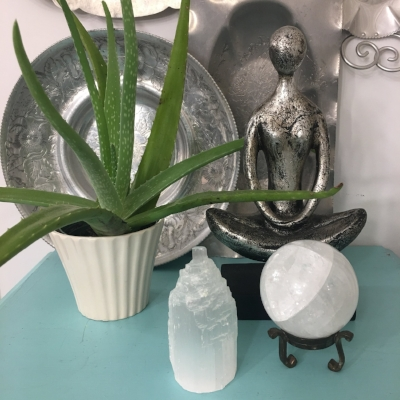 A   yoga statue  , some greenery and a couple of   crystals   create a lovely vignette, as well as, a dedicated space to take some deep breaths, say your mantras, or focus your daily intentions.
