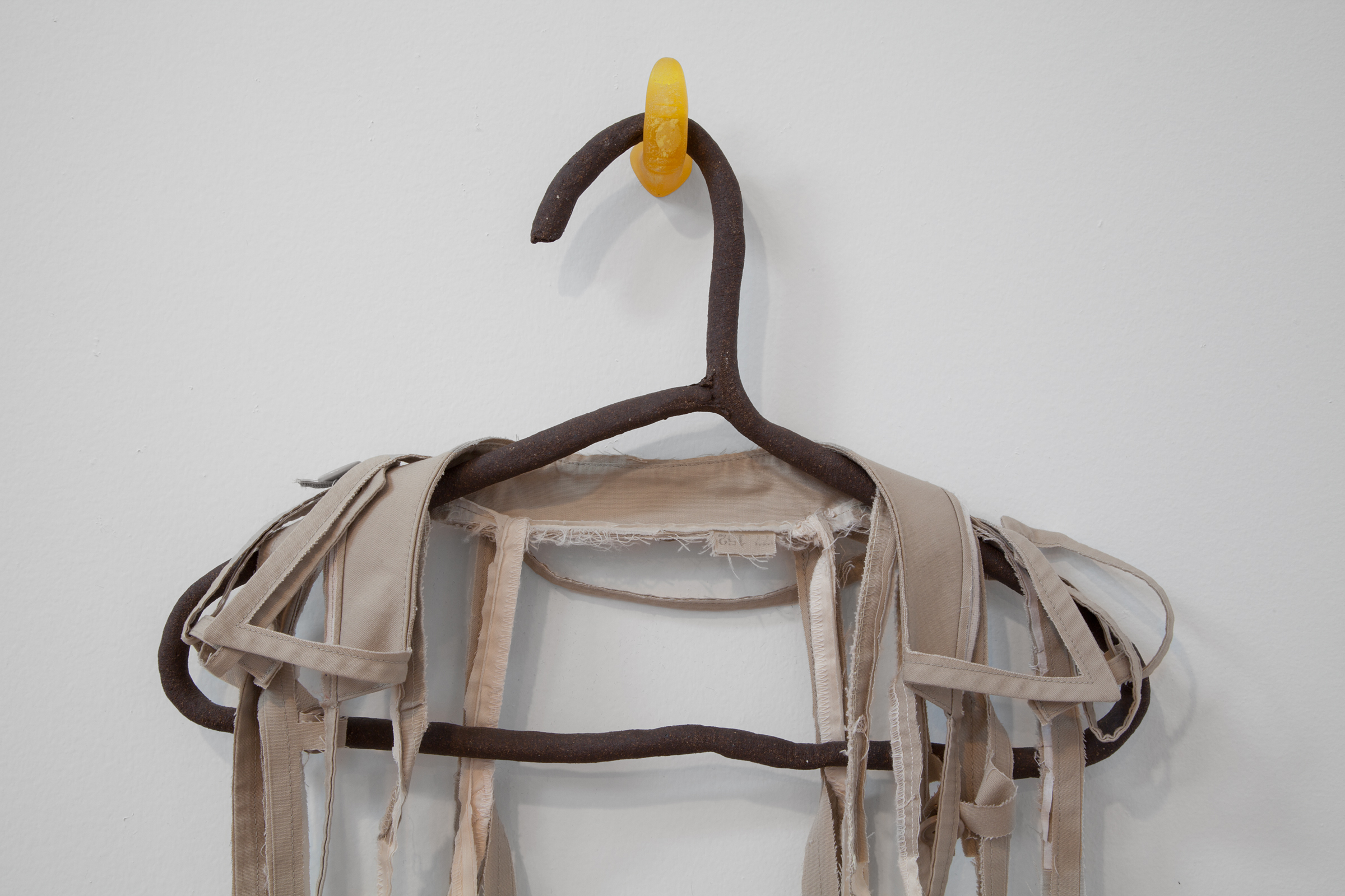 """ANNA SEW HOY  (detail) beige/cream , fired stoneware, trench coat and resin finger hook, 55"""" x 17"""" x 3.5"""", 2012"""