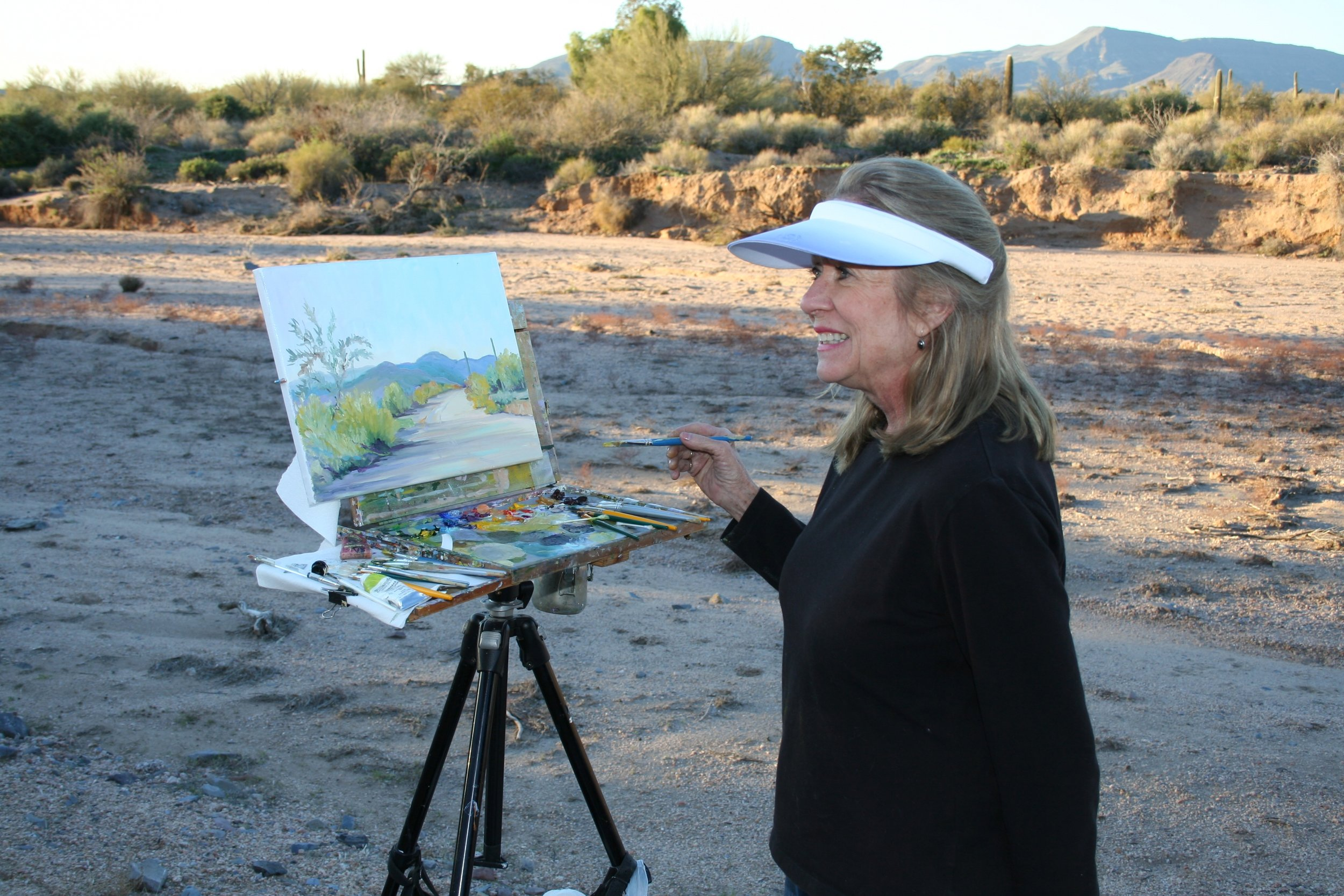 Virginia painting en plein air on the Carefree nature preserve behind her home.